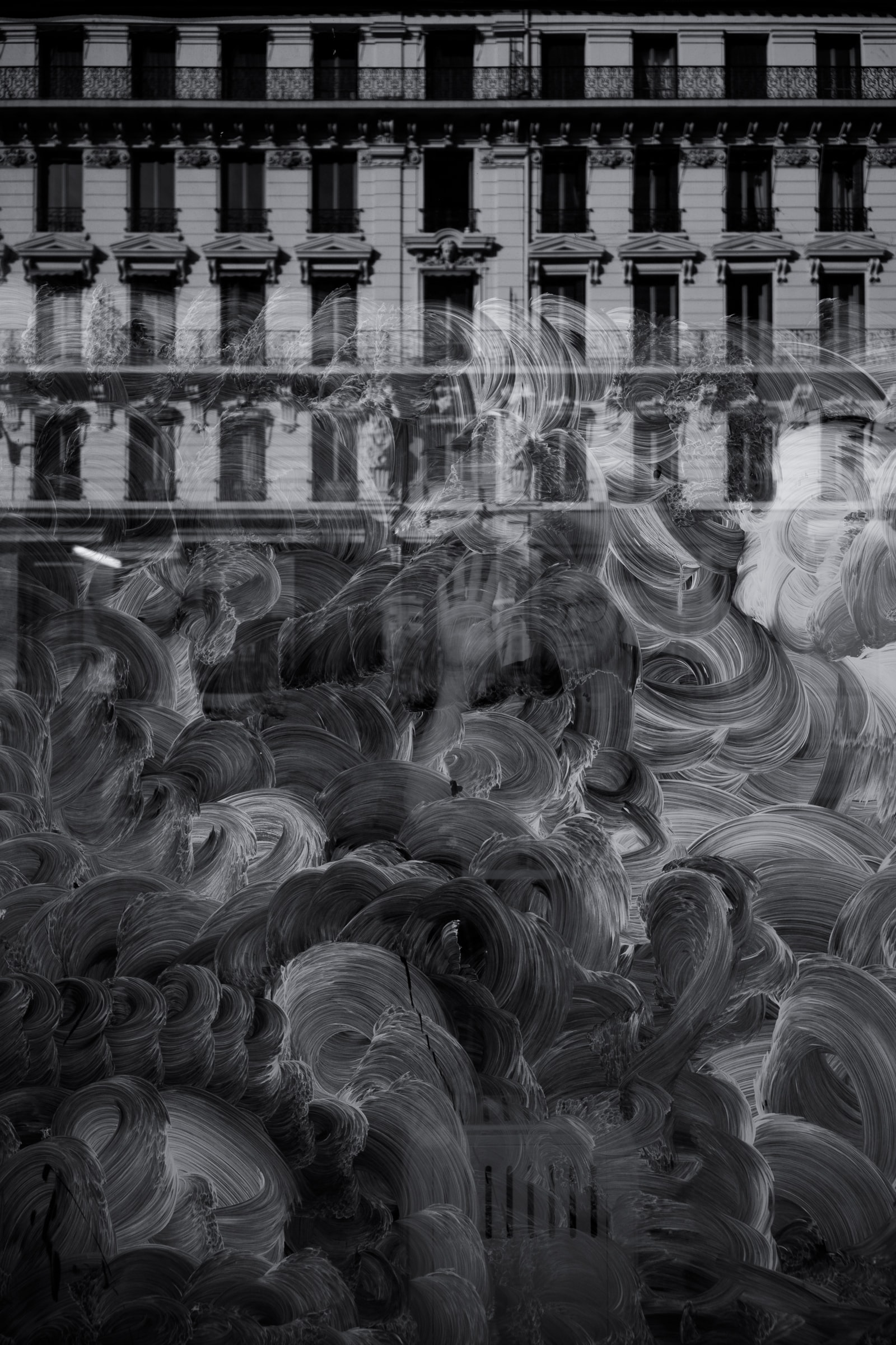 A black-and-white shot of a building facade reflected in a smeared window in Lyon