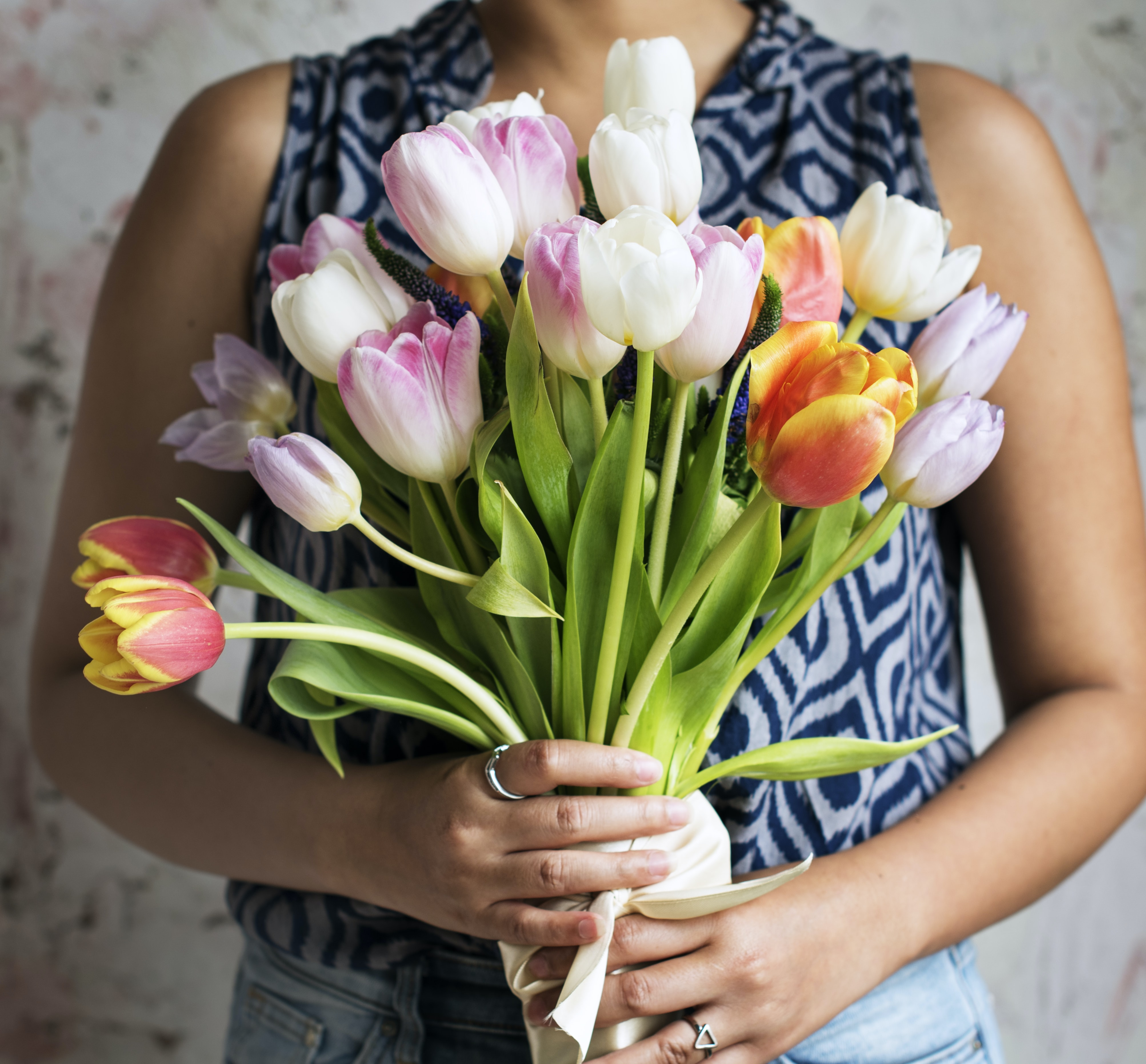 A woman holding a large bouquet of tulips in front of her chest