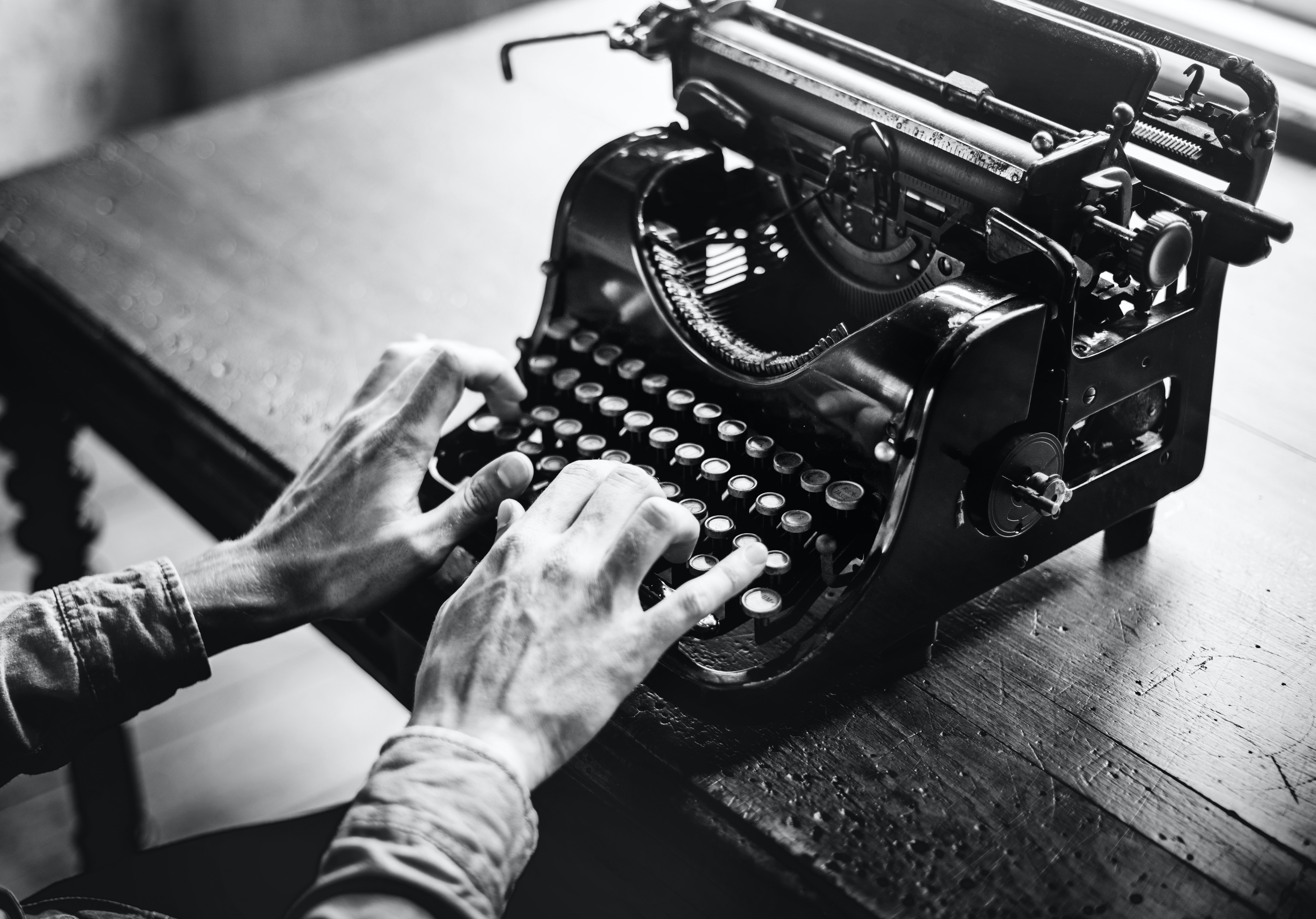 person using typewriter on brown wooden table
