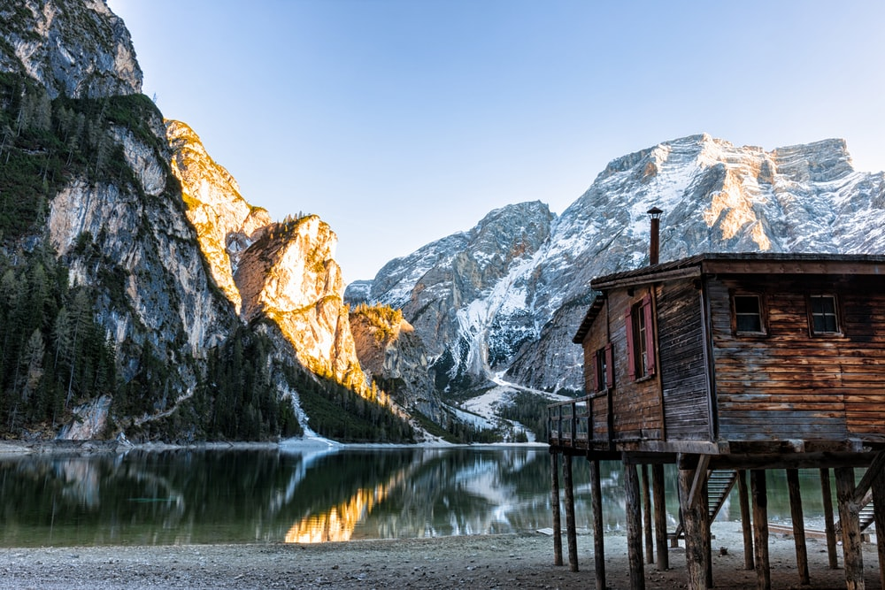 brown cabin beside lake
