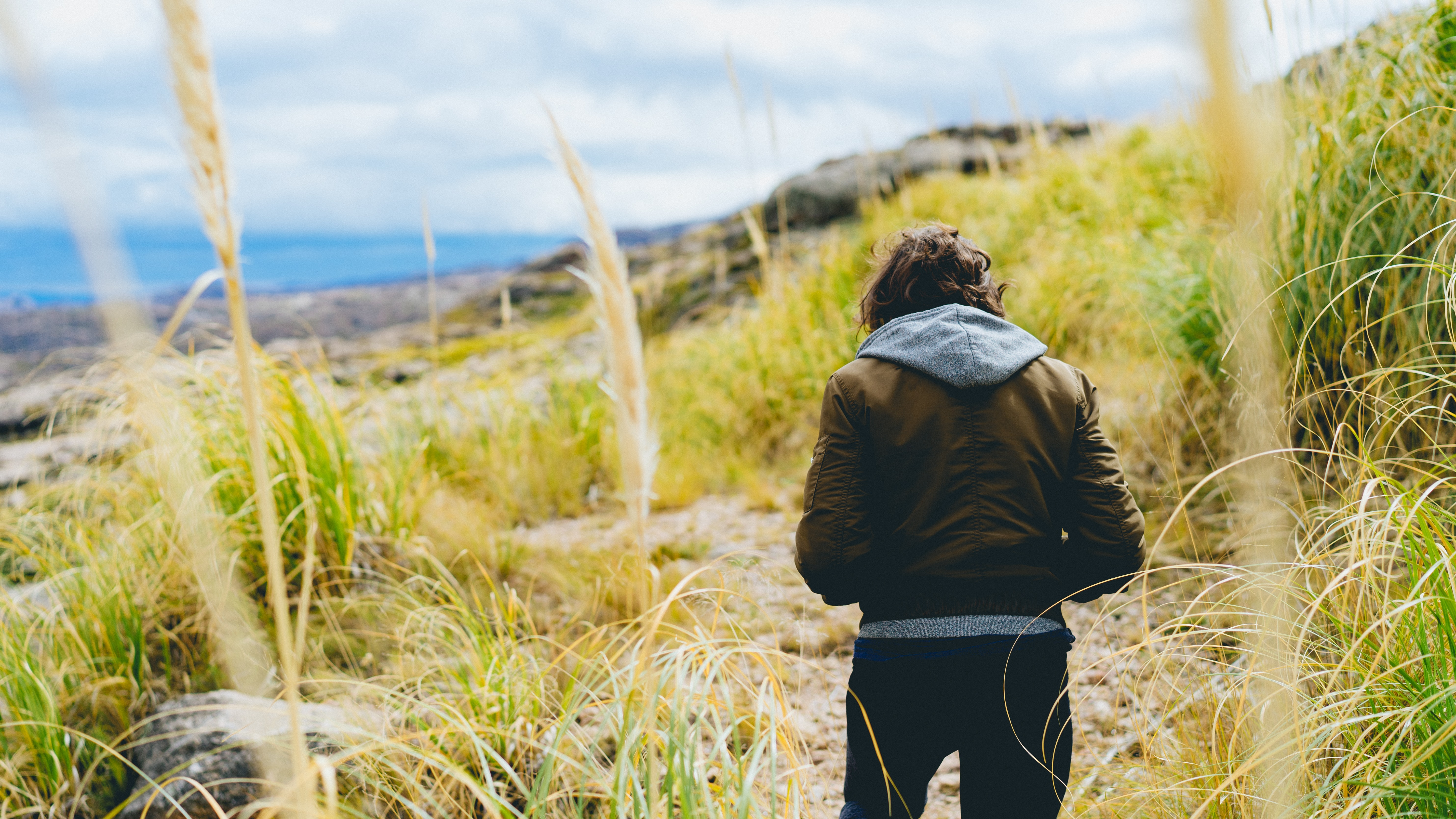 Person in a brown leather jacket and gray hoodie in field of wheat beside the sea