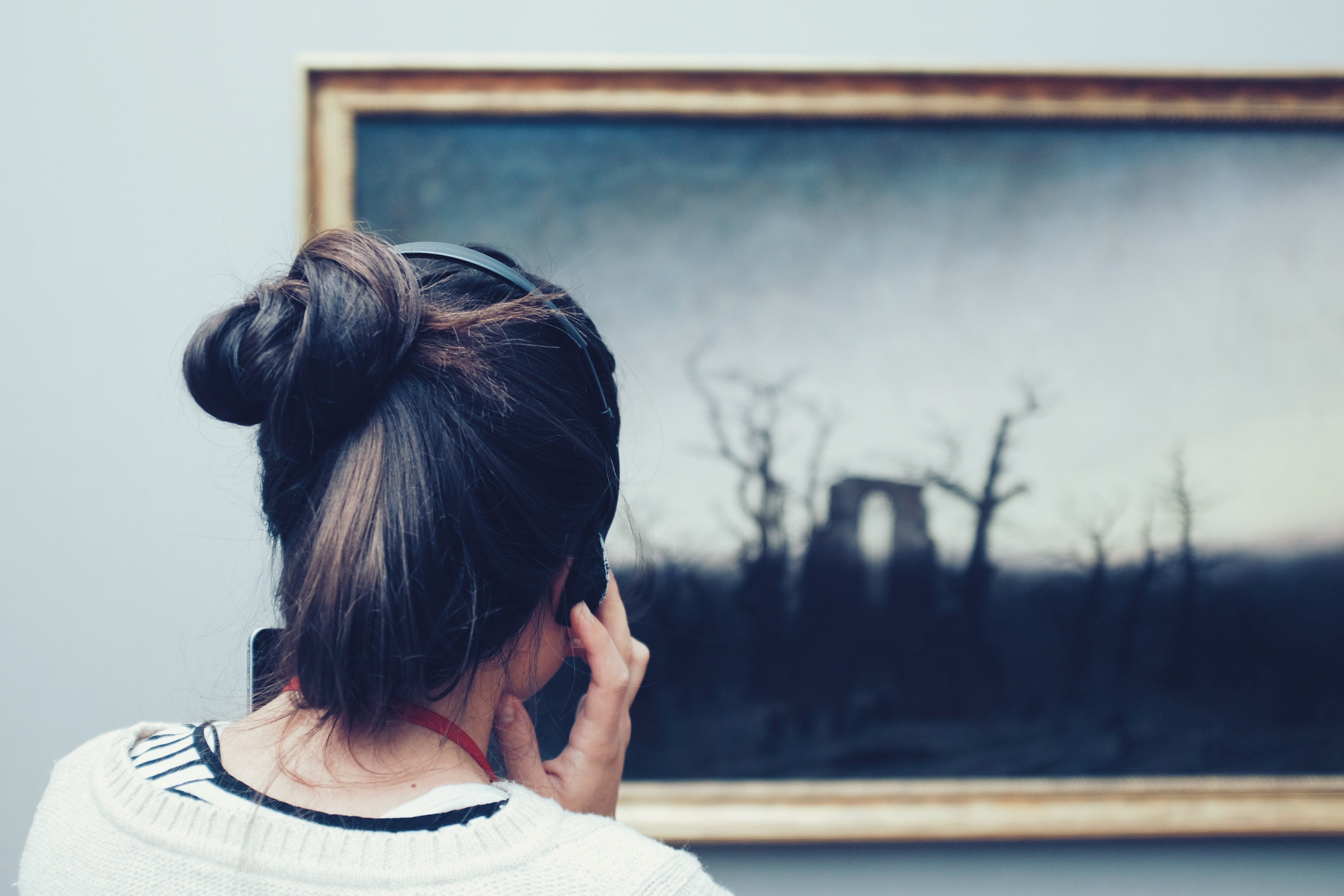 Woman on a museum audio tour looking at a painting and listening through headphones