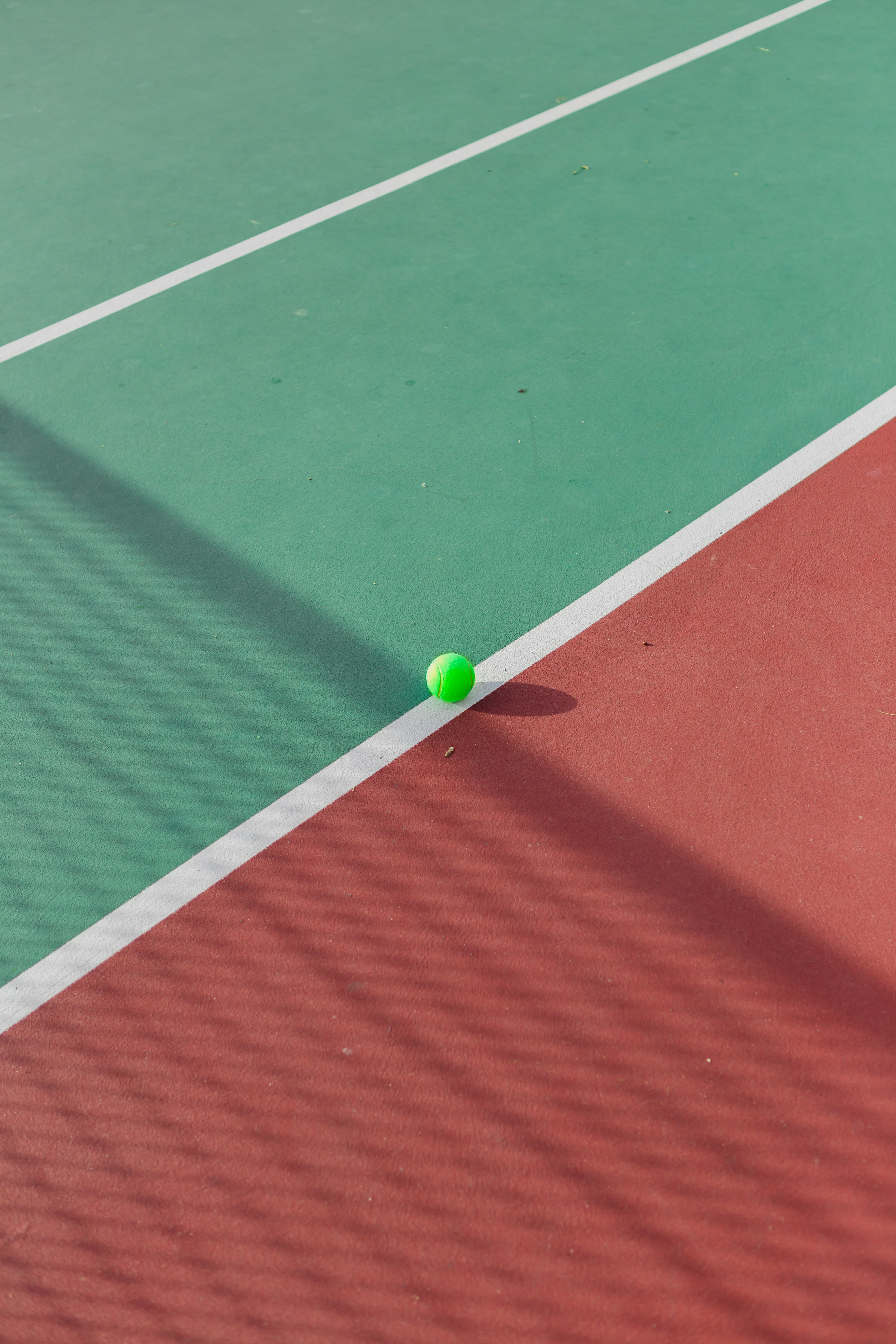 A tennis ball just crossing the line on a tennis court.