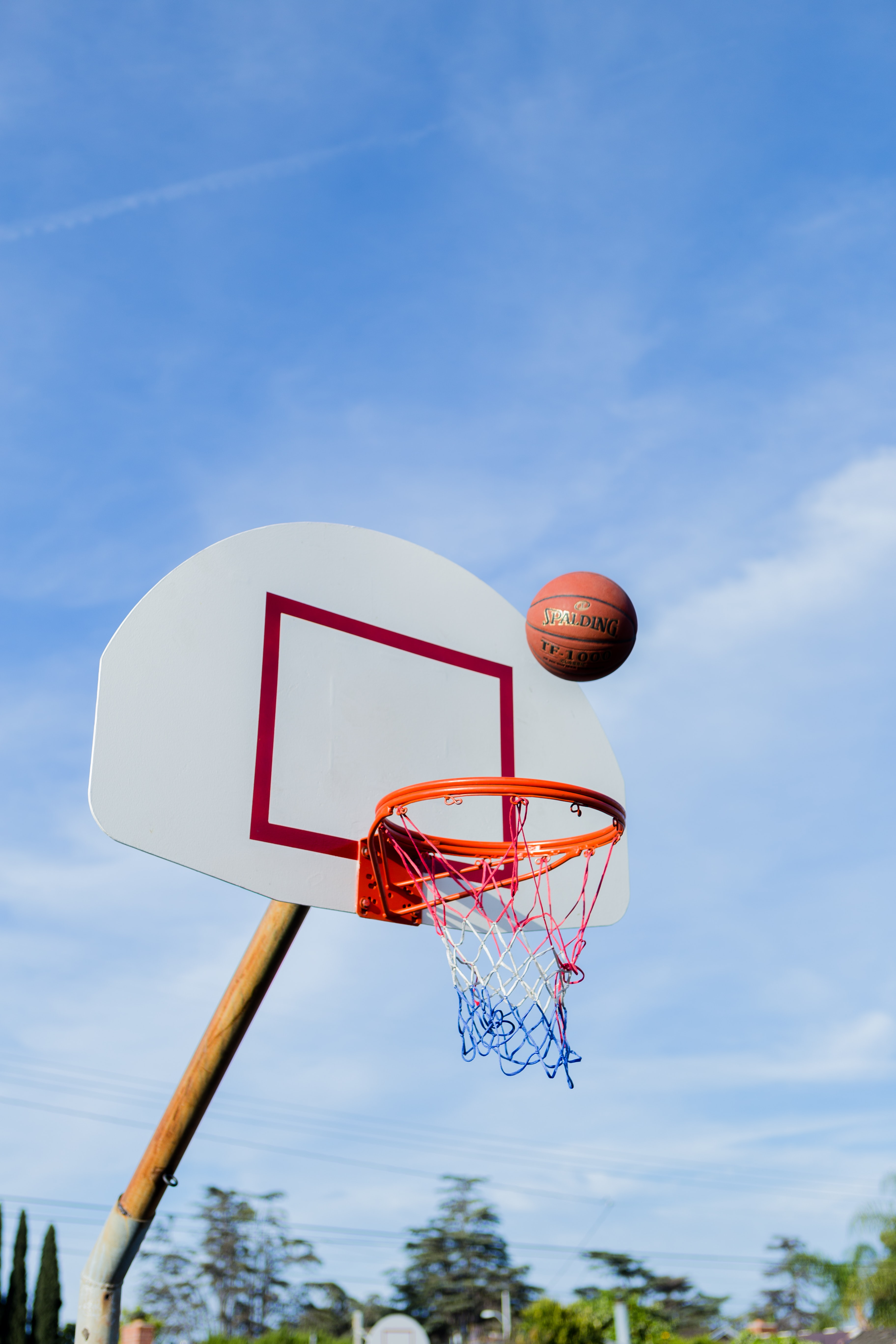A basketball about to enter a bball net in an outdoor court.