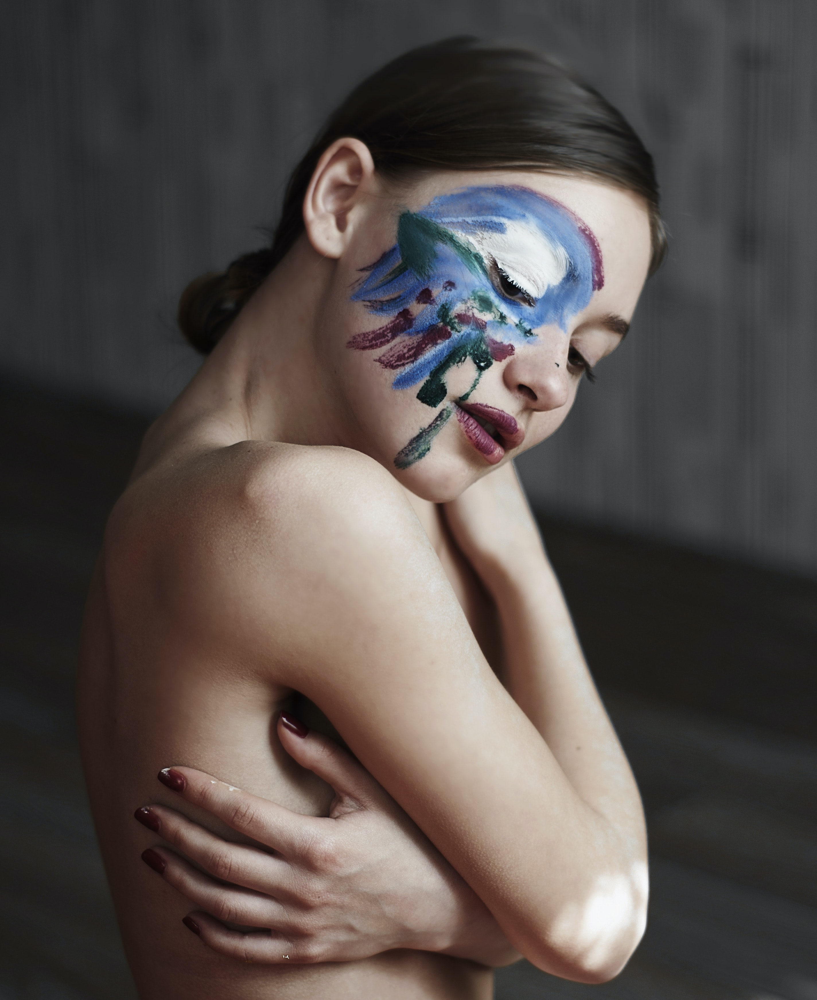 Woman posing topless with artistic body pain on her face