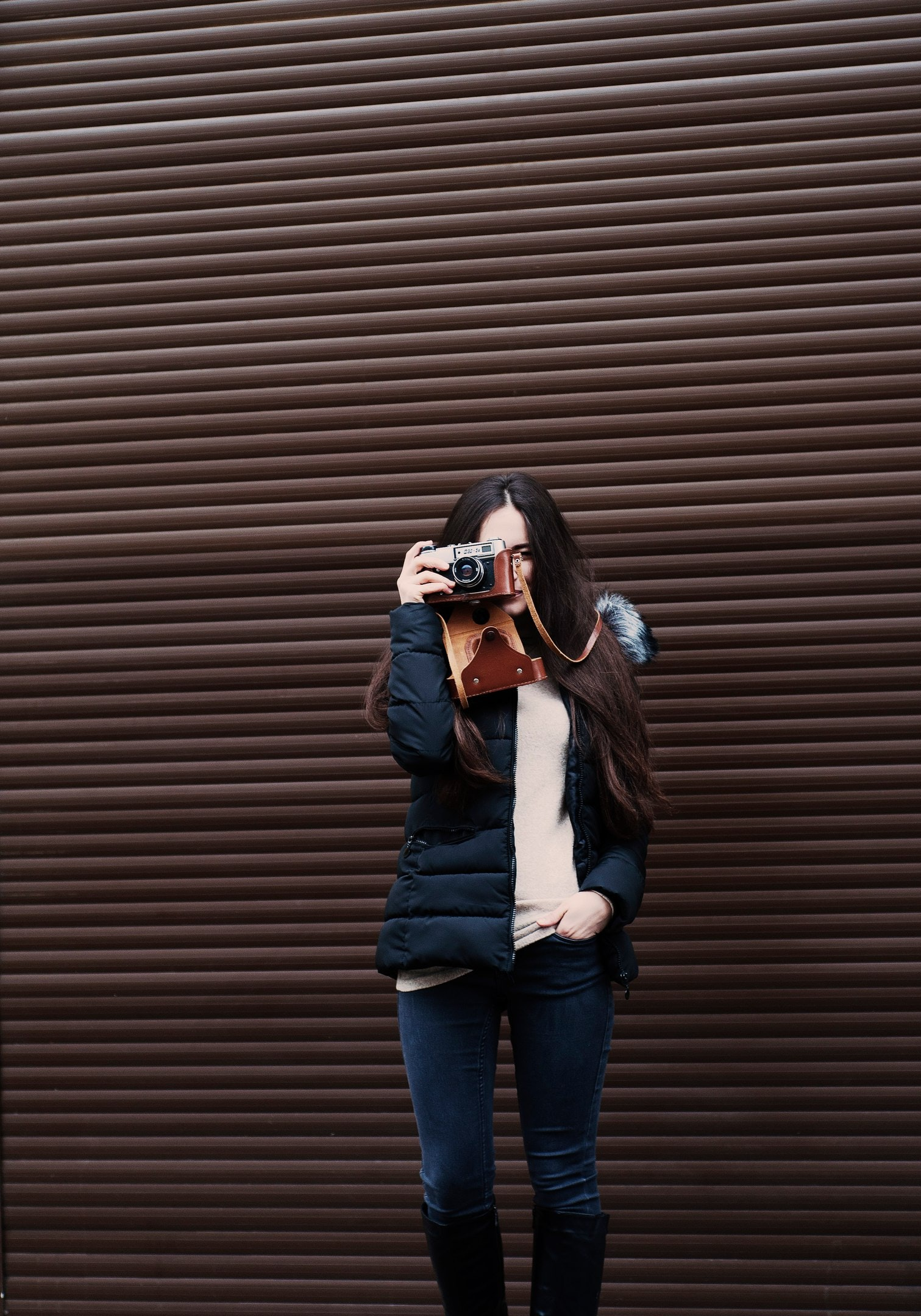 Woman takes a picture with a vintage camera outside
