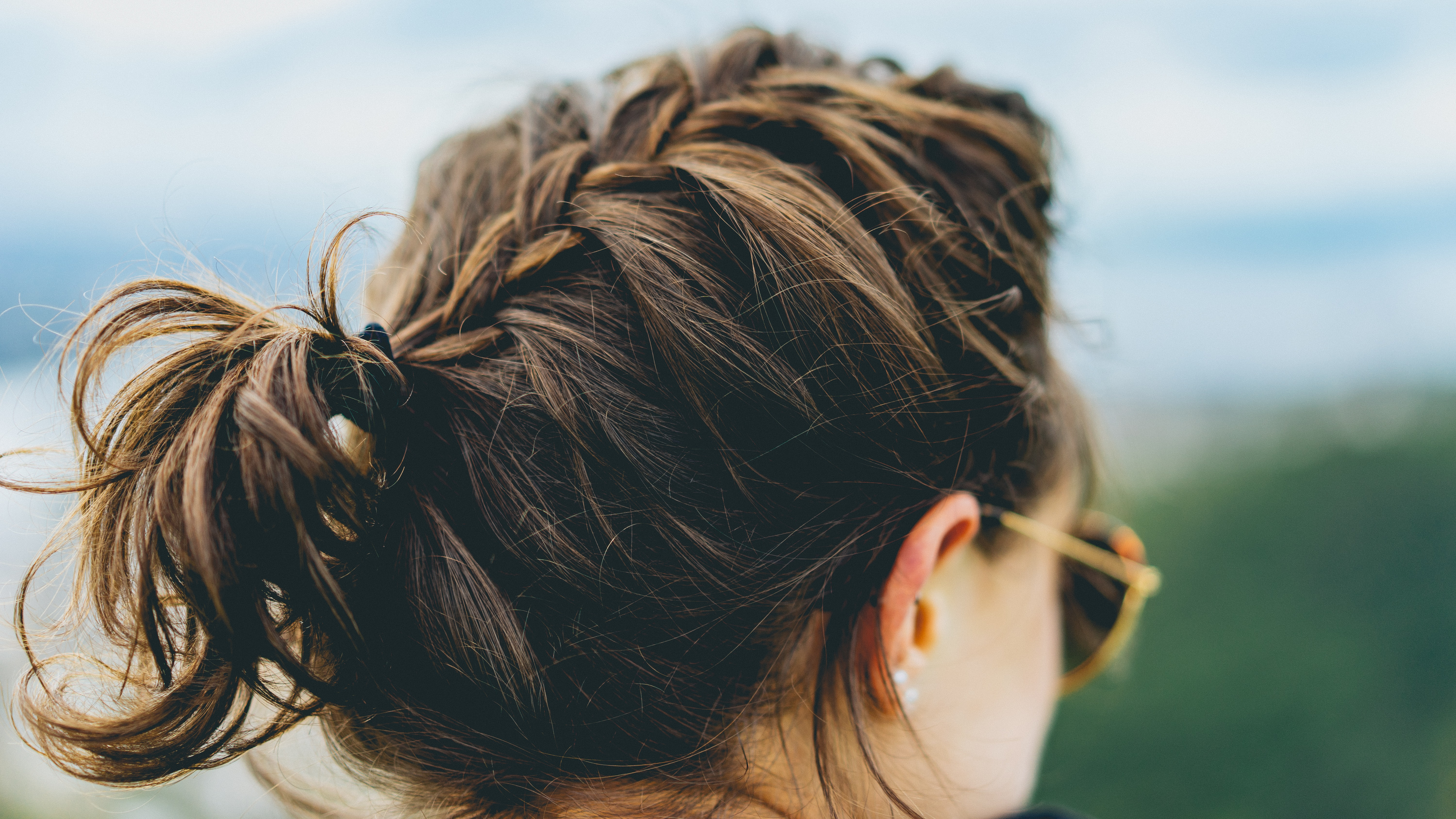 A woman with a braid in sunglasses faces away from the camera against a blue sky