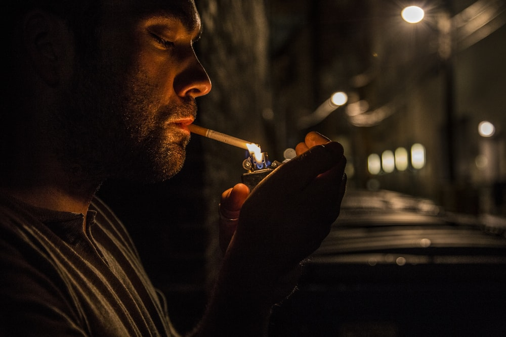 man lighting up flip-top lighter for cigar