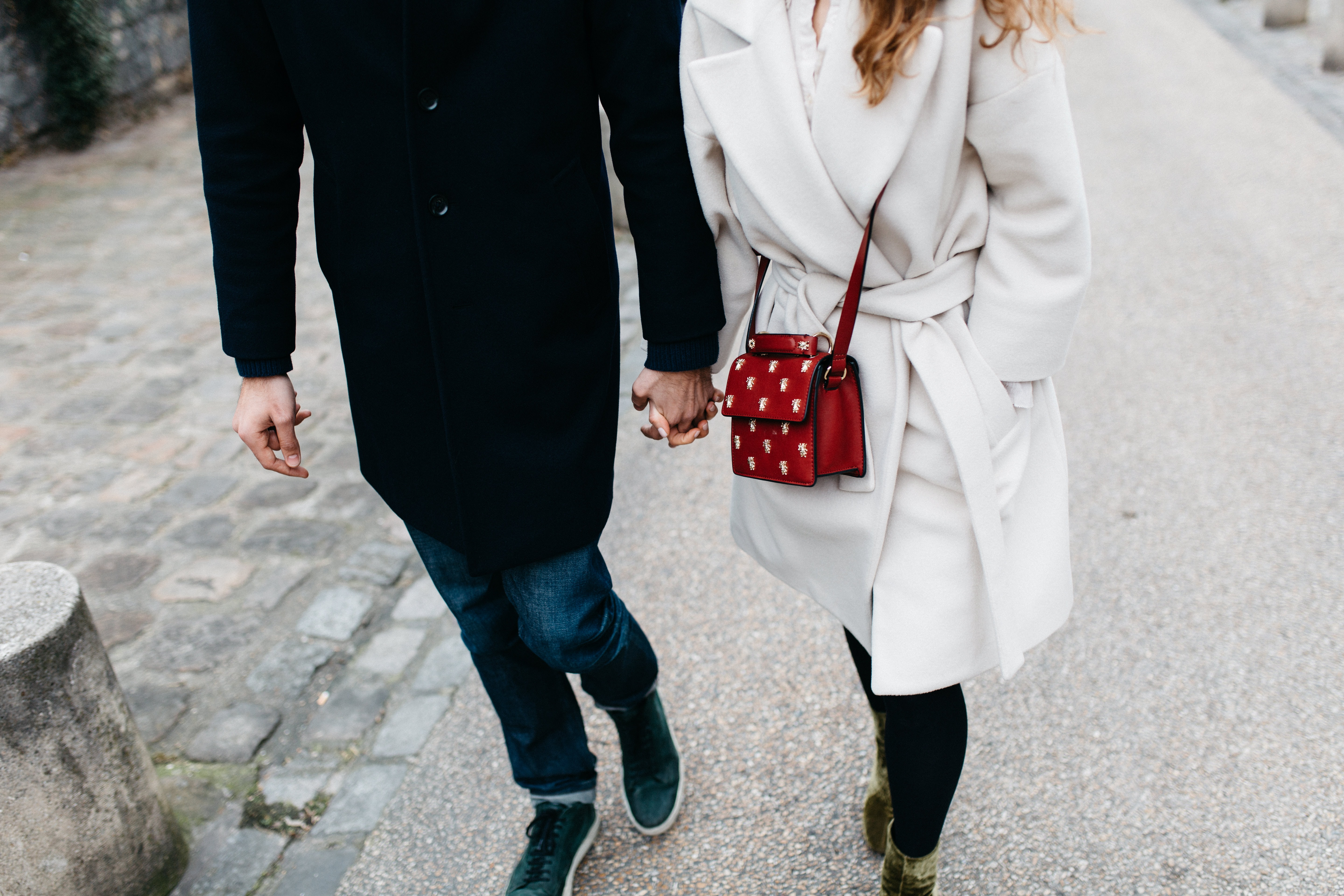 A fashionable couple holding hands while walking on the street.