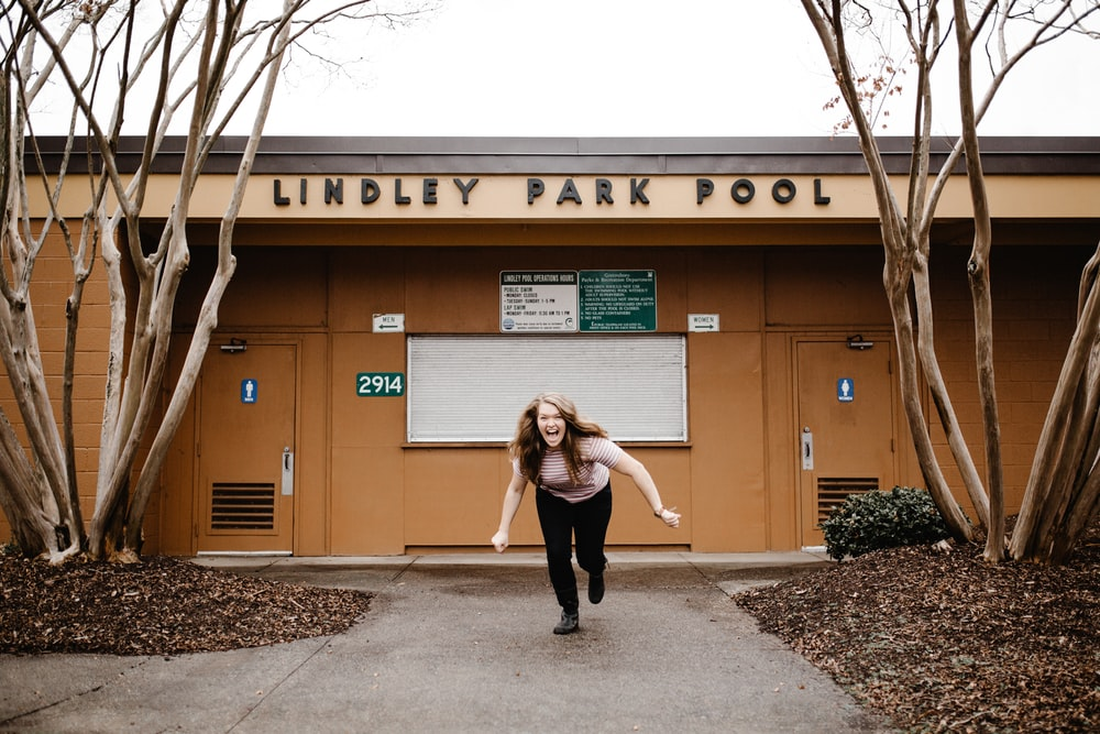 woman laughing and running in front of Lindley Park Pool building during day