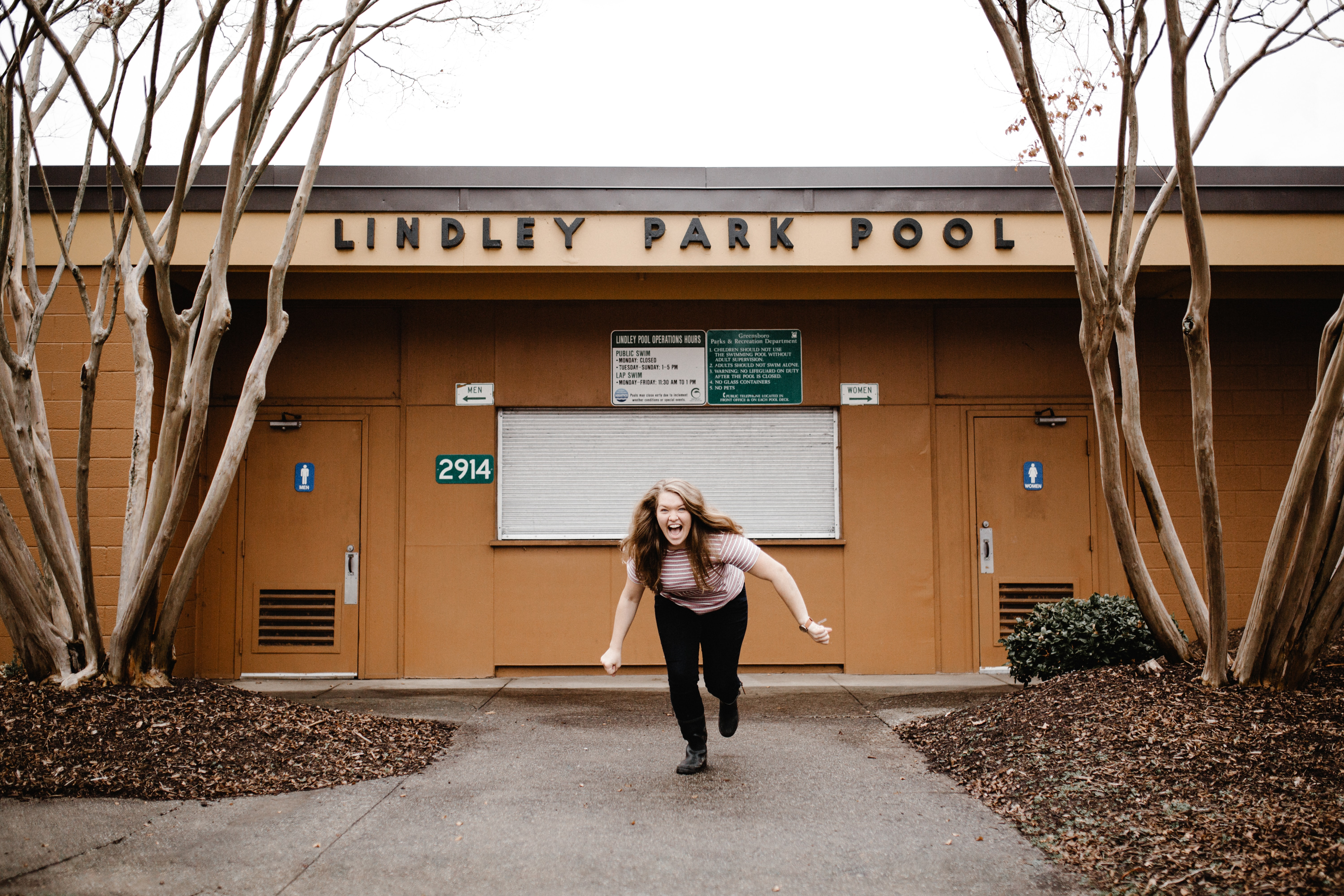 A woman laughs while lunging forward in front of the bathrooms at the Lindley Park pool