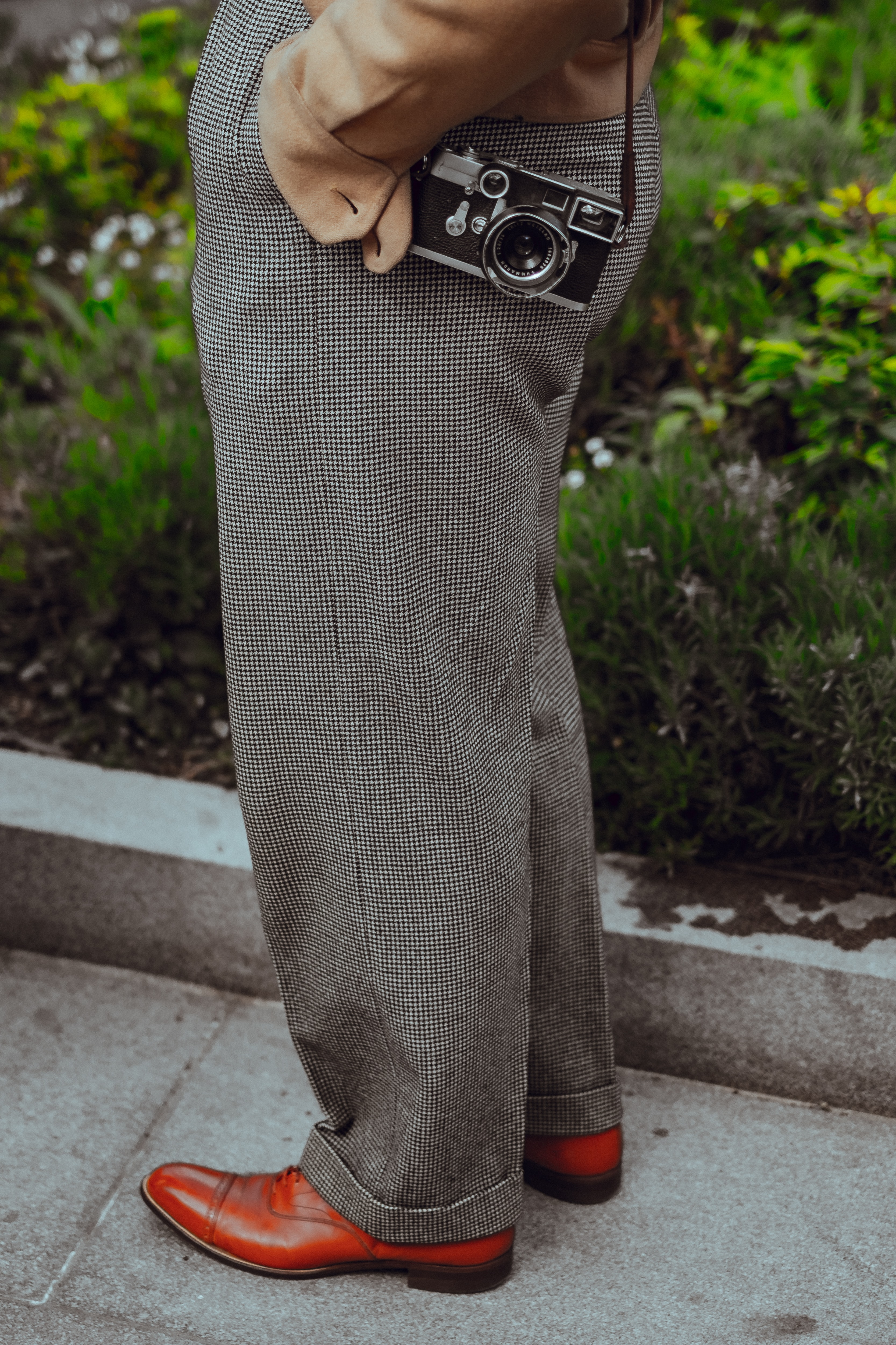 person wearing gray dress pants with camera