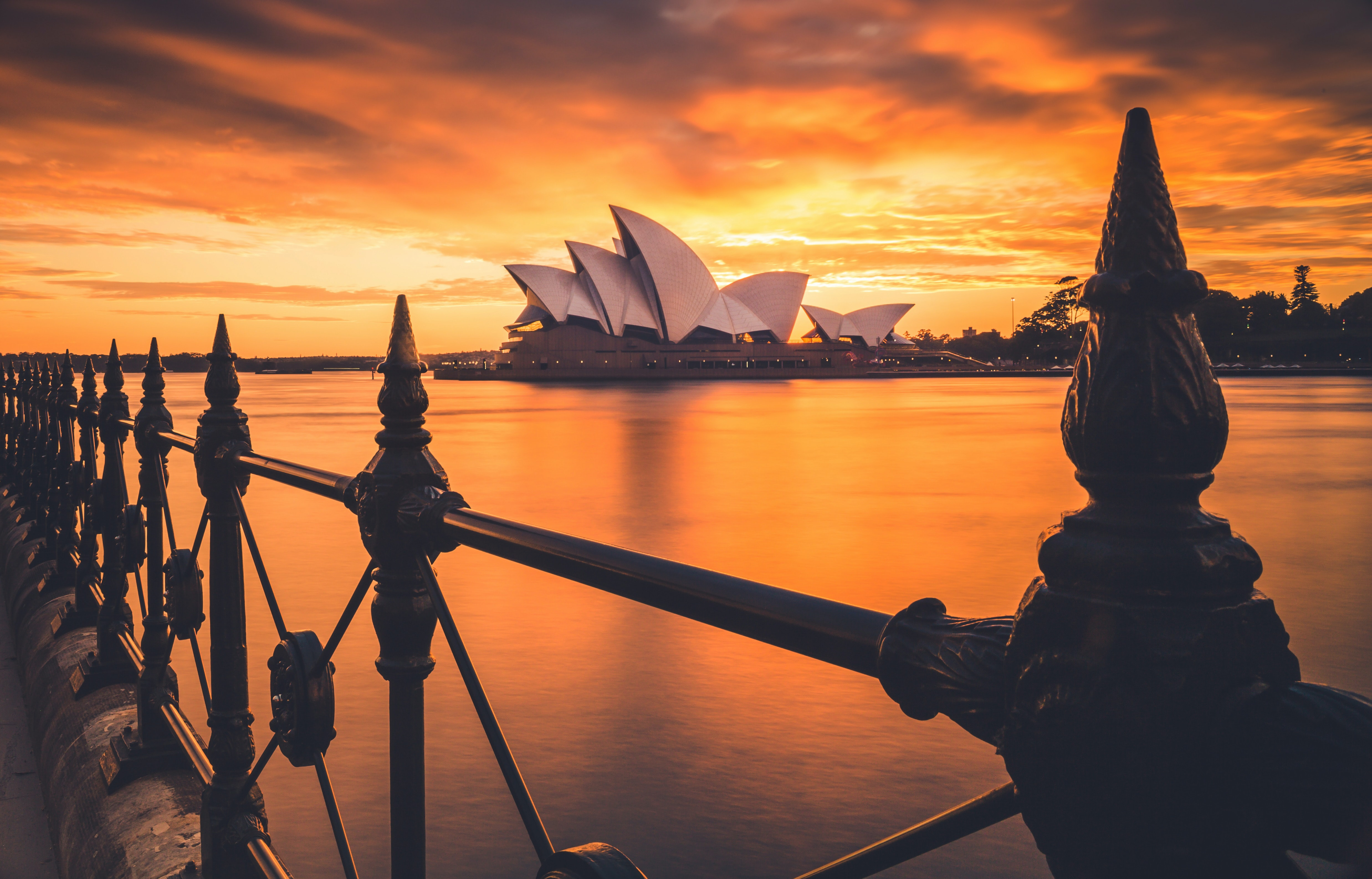 Railing in Sidney with an orange sky during sunset and an opera in the background