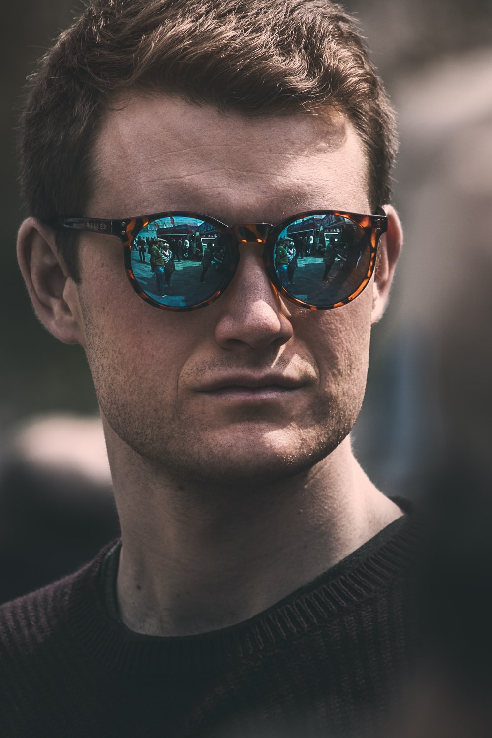 143c7c990 Man in reflective hipster sunglasses looking out at a busy city ...