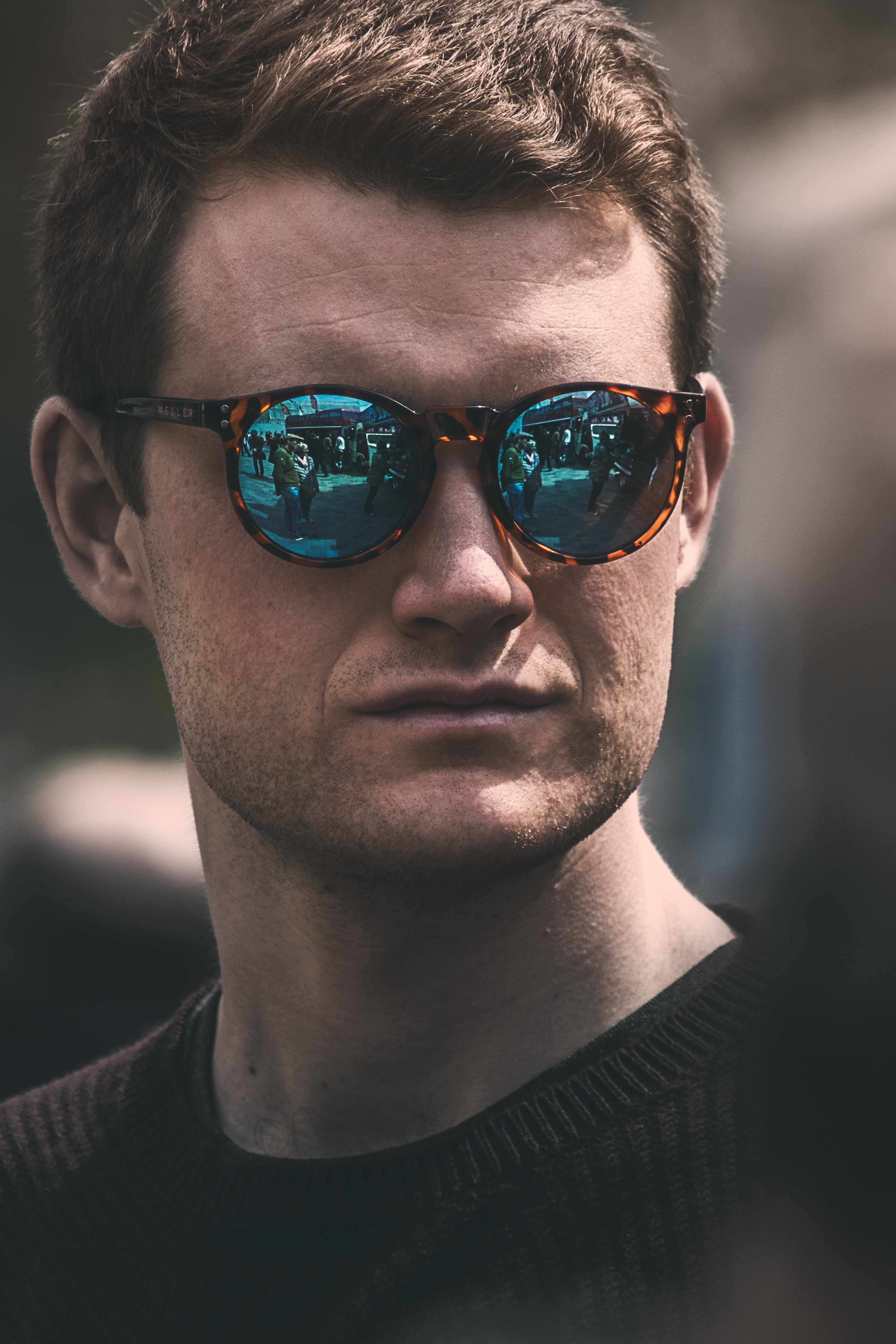 Man in reflective hipster sunglasses looking out at a busy city