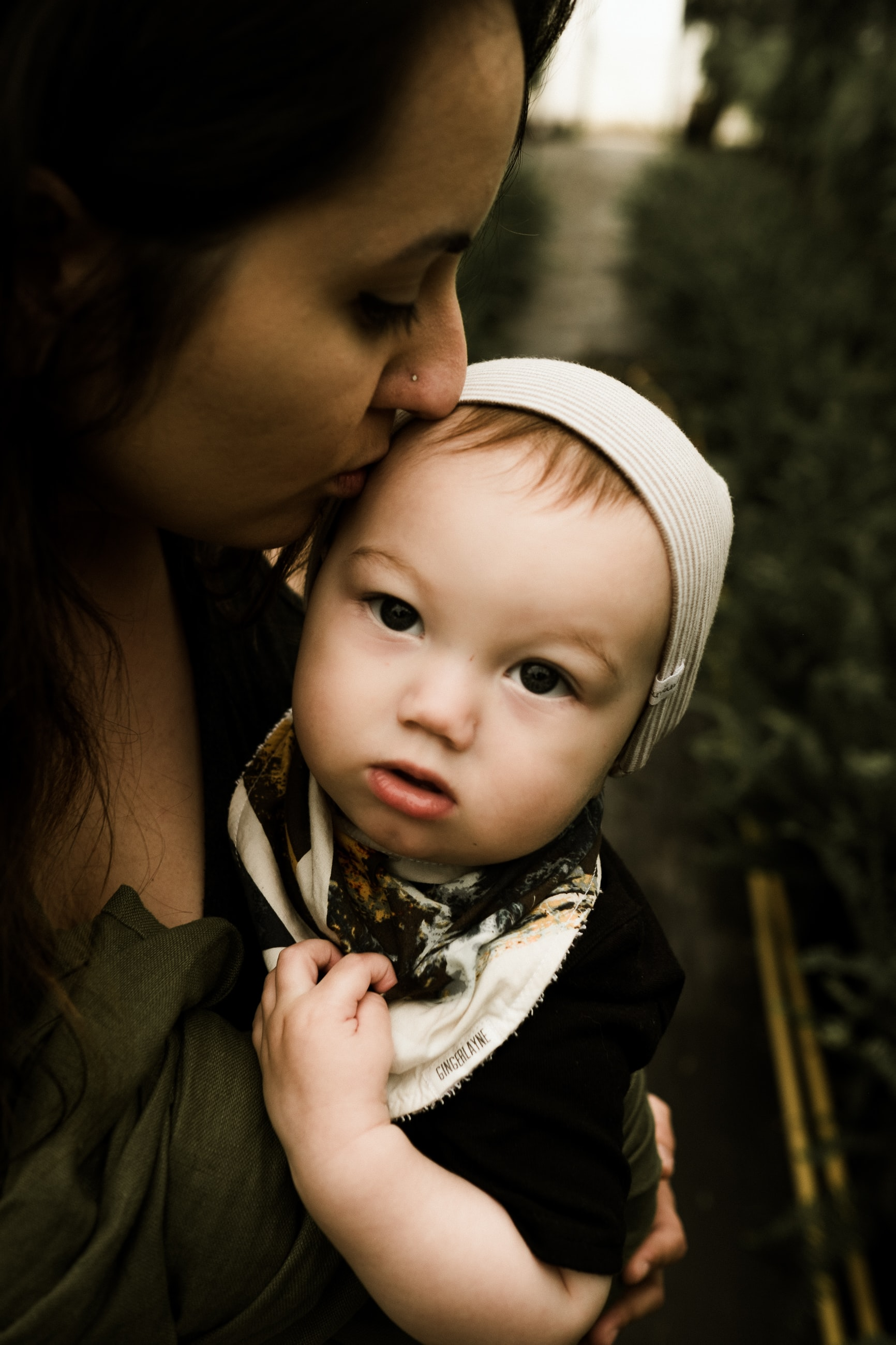 A brunette mother affectionately kissing the forehead of her young toddler, who is wearing a white hat