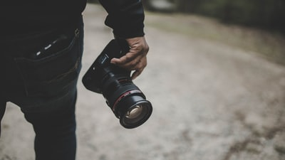 person holding dslr camera photographer zoom background