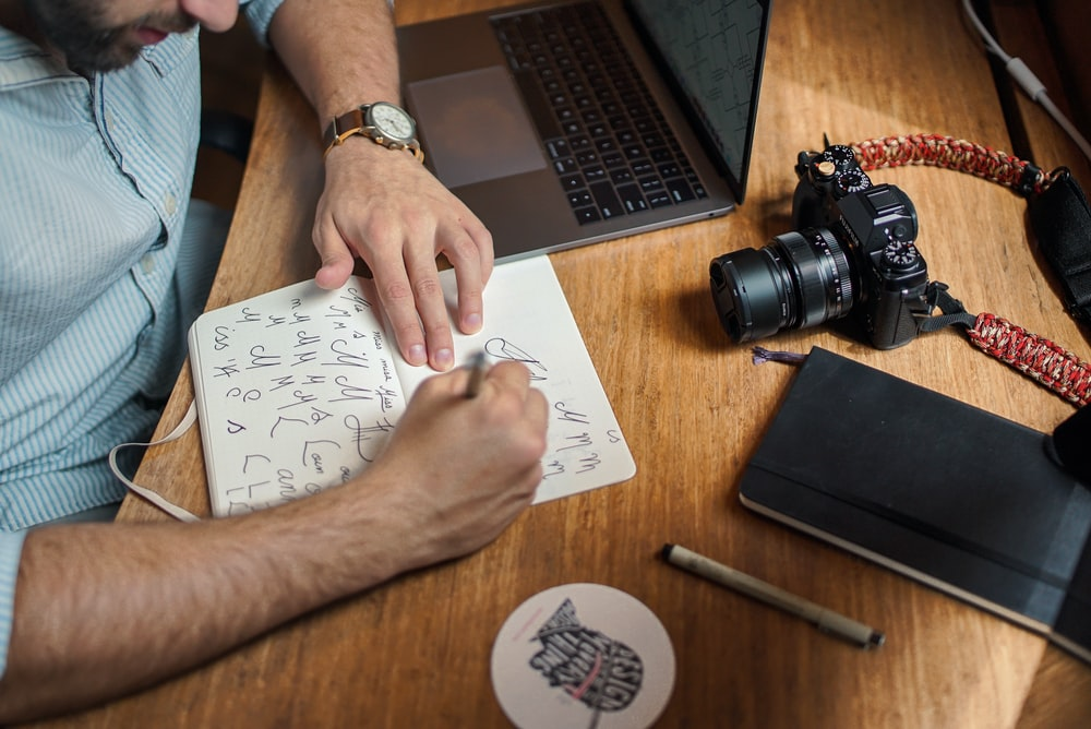 man writing on paper in front of DSLR