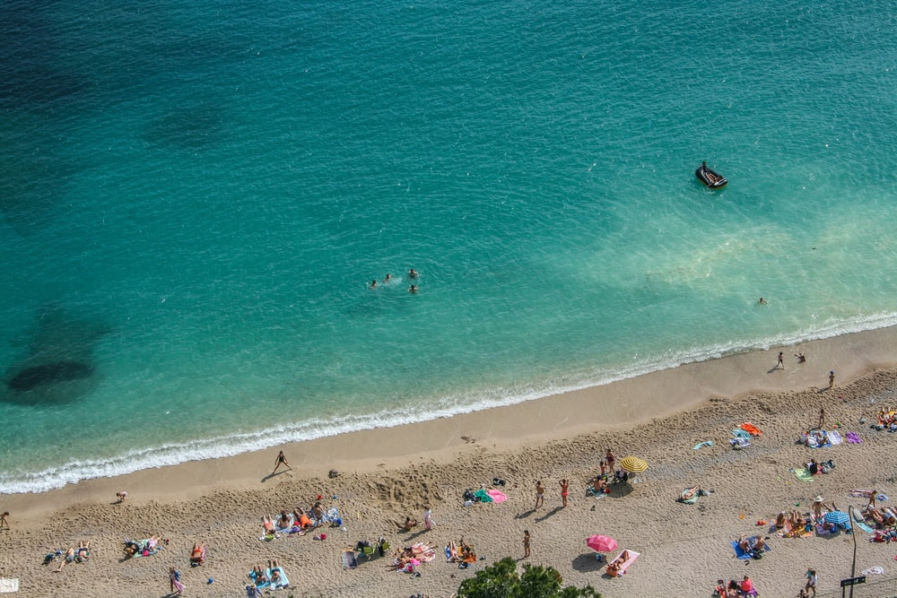 An aerial shot of people sunbathing on a wet beach with a group of friends swimming in the sea