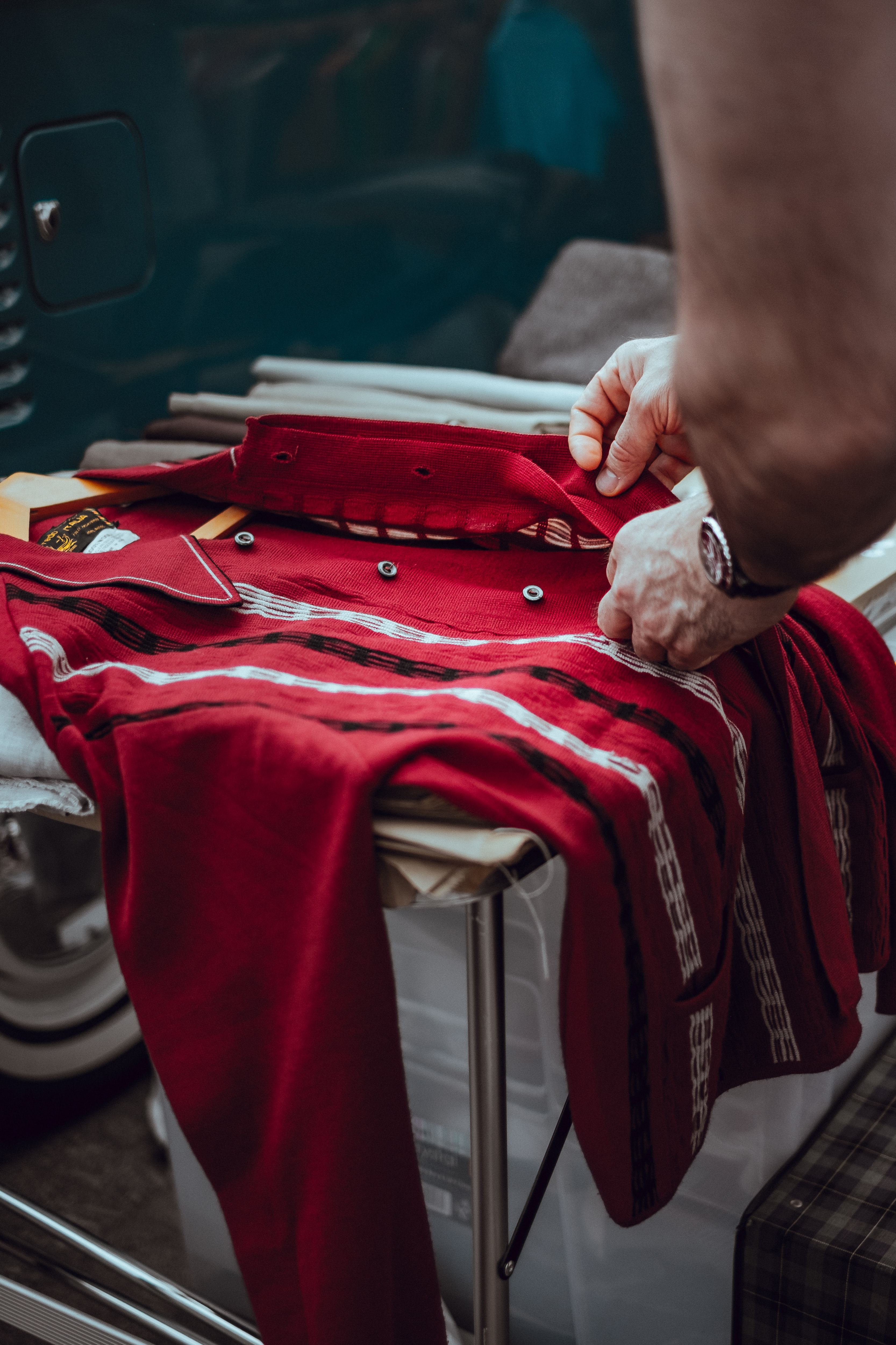 A person examines a red vintage garment on a table in Lewis Cubitt Square