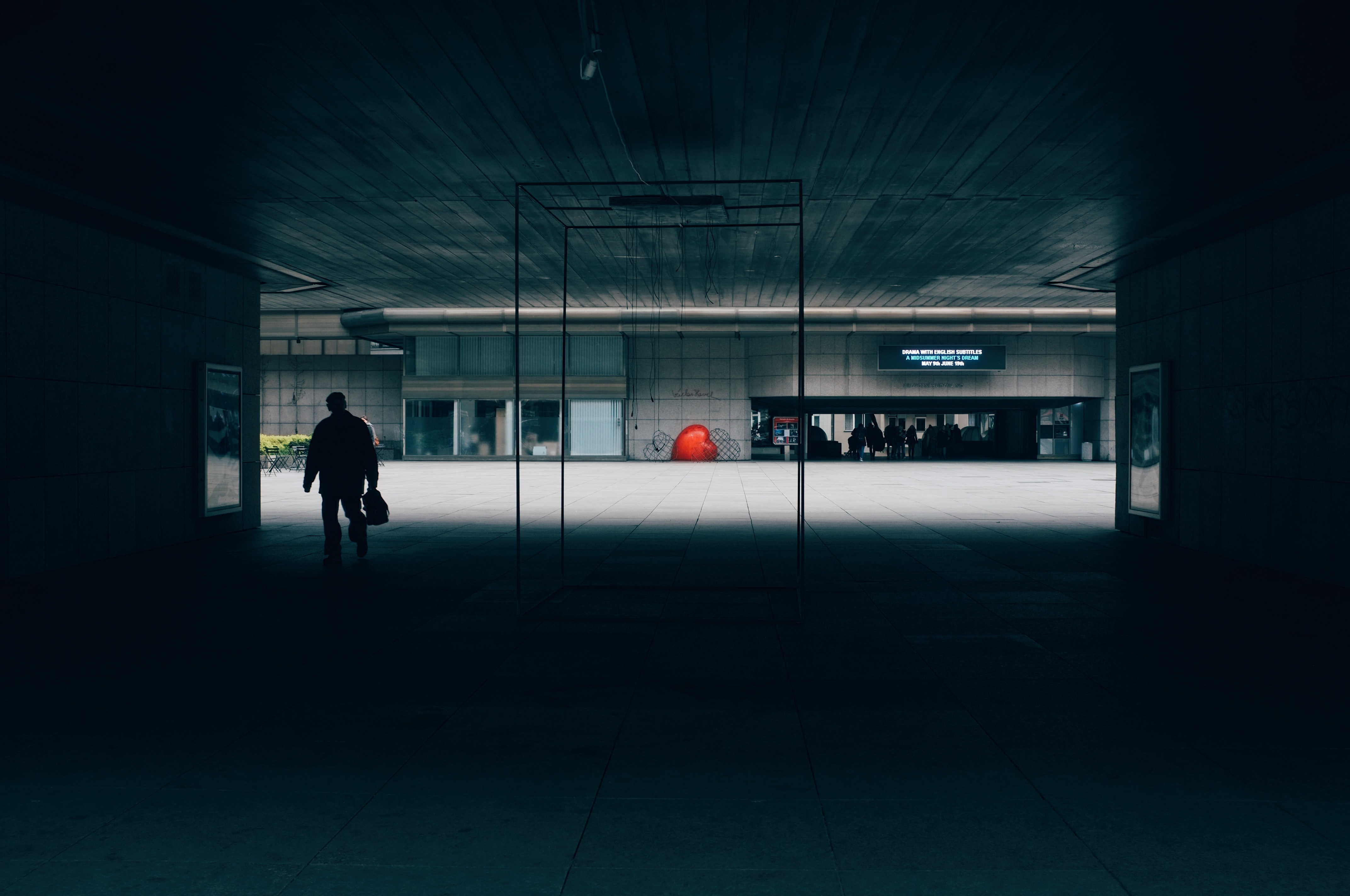 A silhouette of a person in a dimly lit underground passage