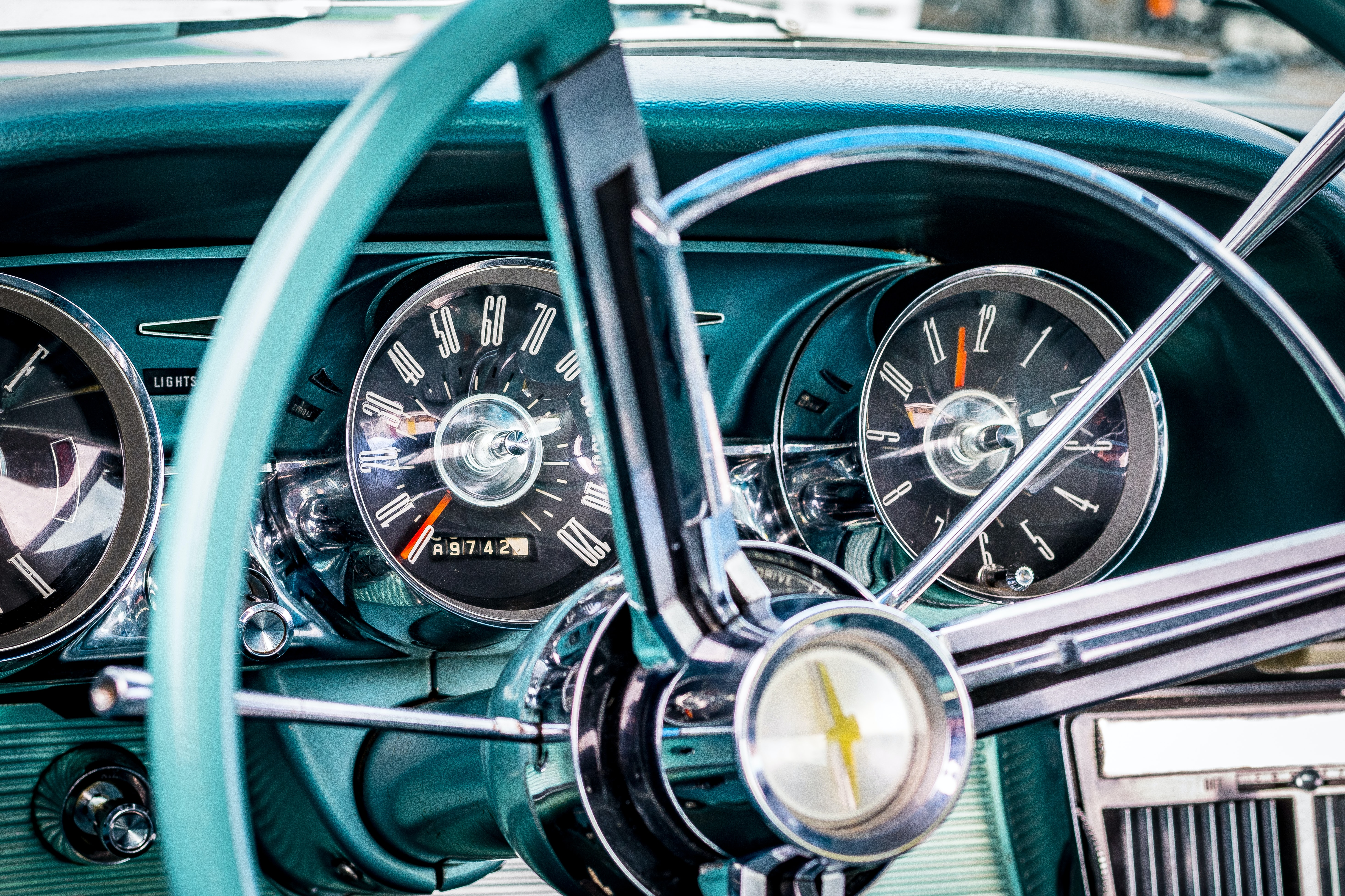 Macro shot of a turquoise-colored vintage steering wheel and dashboard.