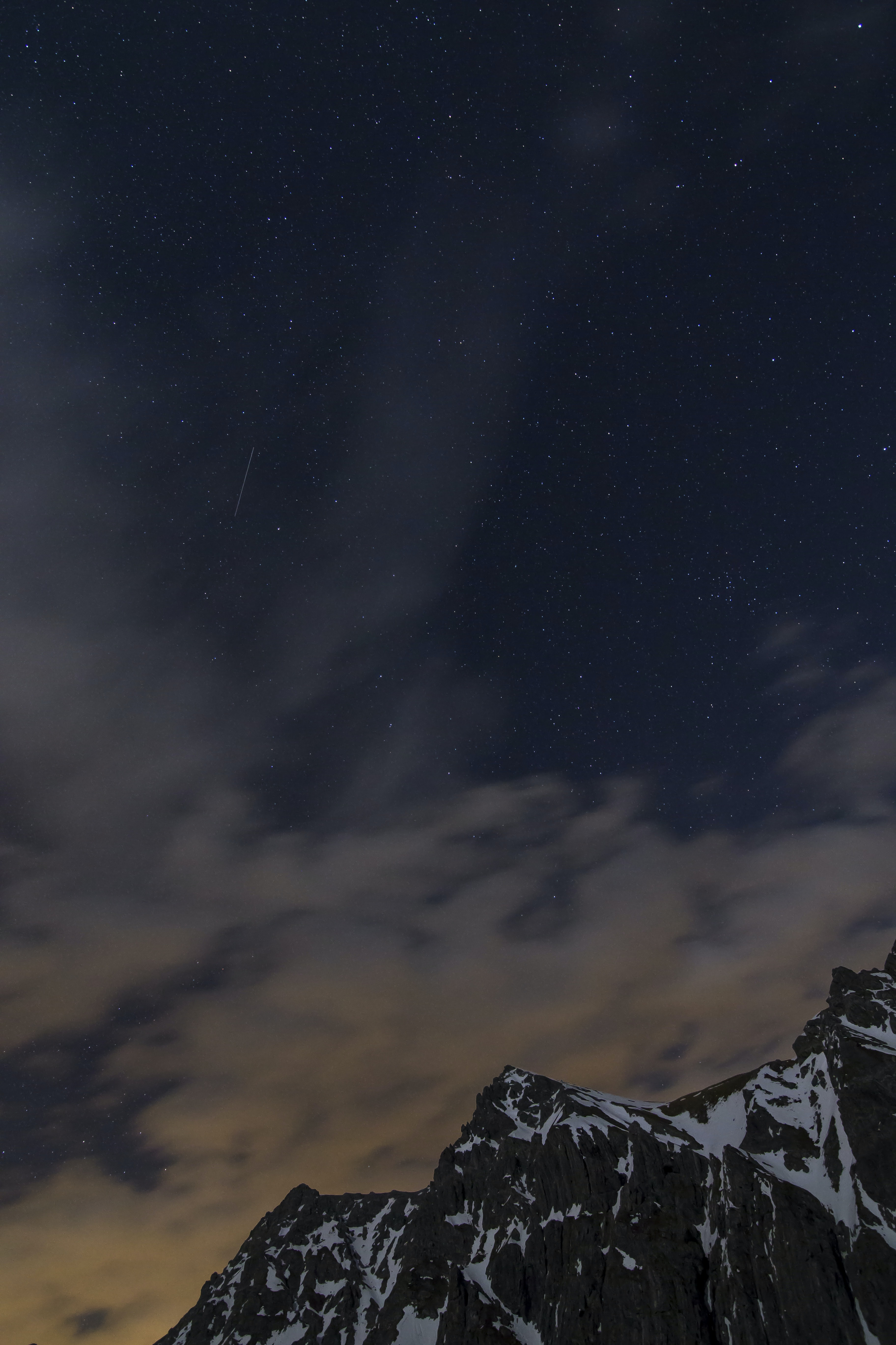 Clouds obscure the starry sky over tall mountain peaks near Lünersee