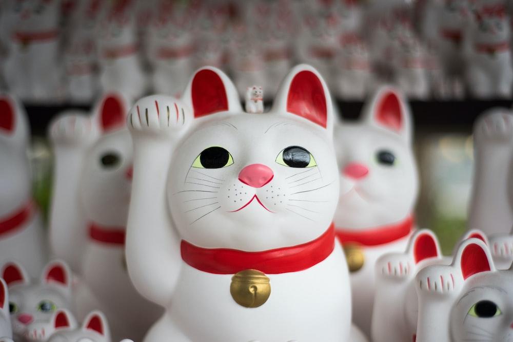 A Number Of Japanese Maneki Neko Figurines Depicting Beckoning White Cat