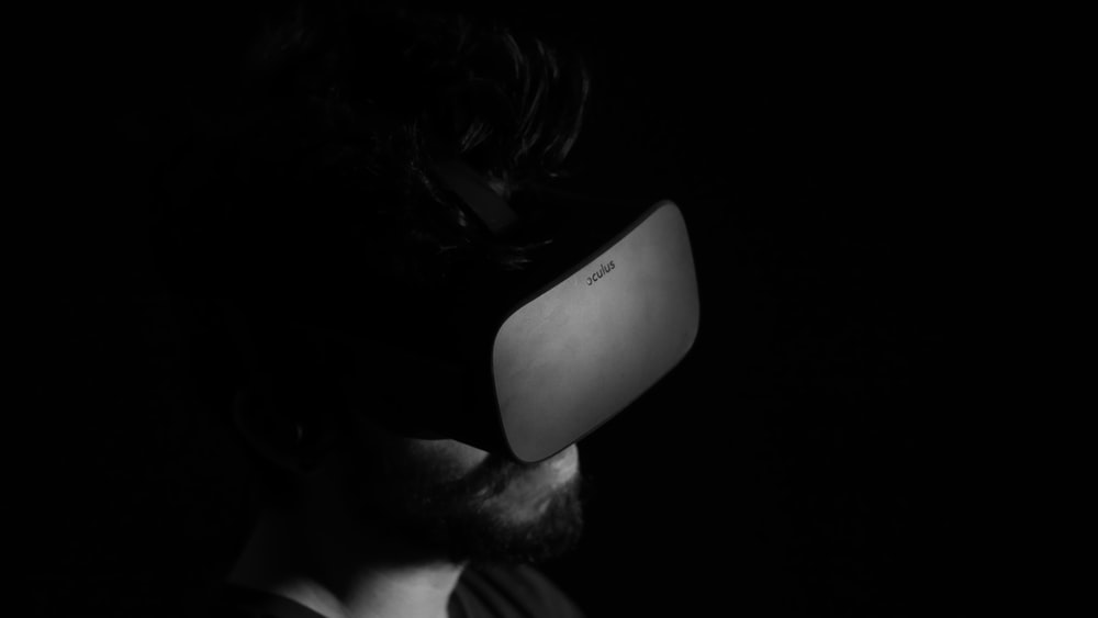 grayscale photo of man using virtual reality headset