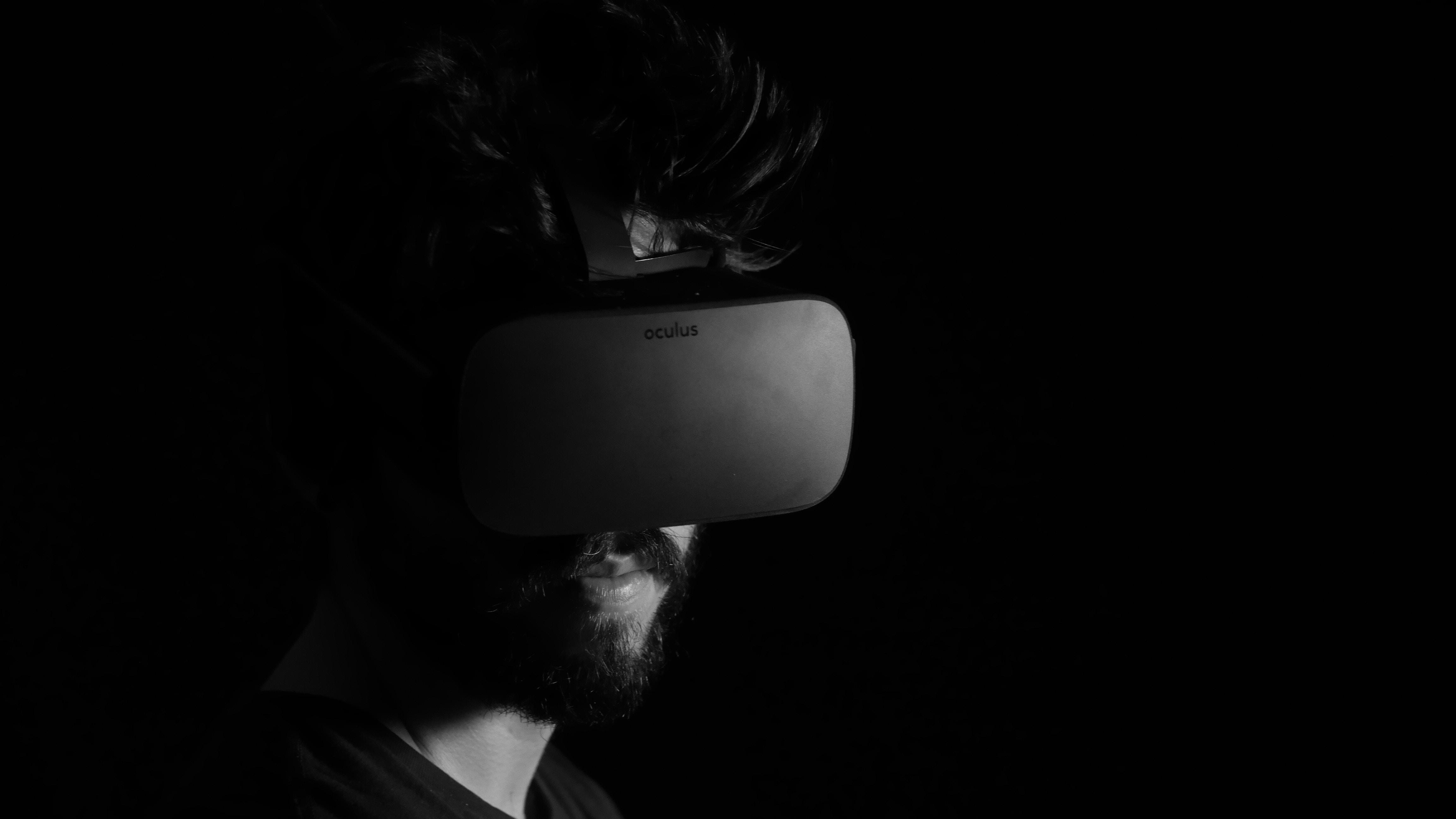A dark photo of a man wearing a virtual reality visor.