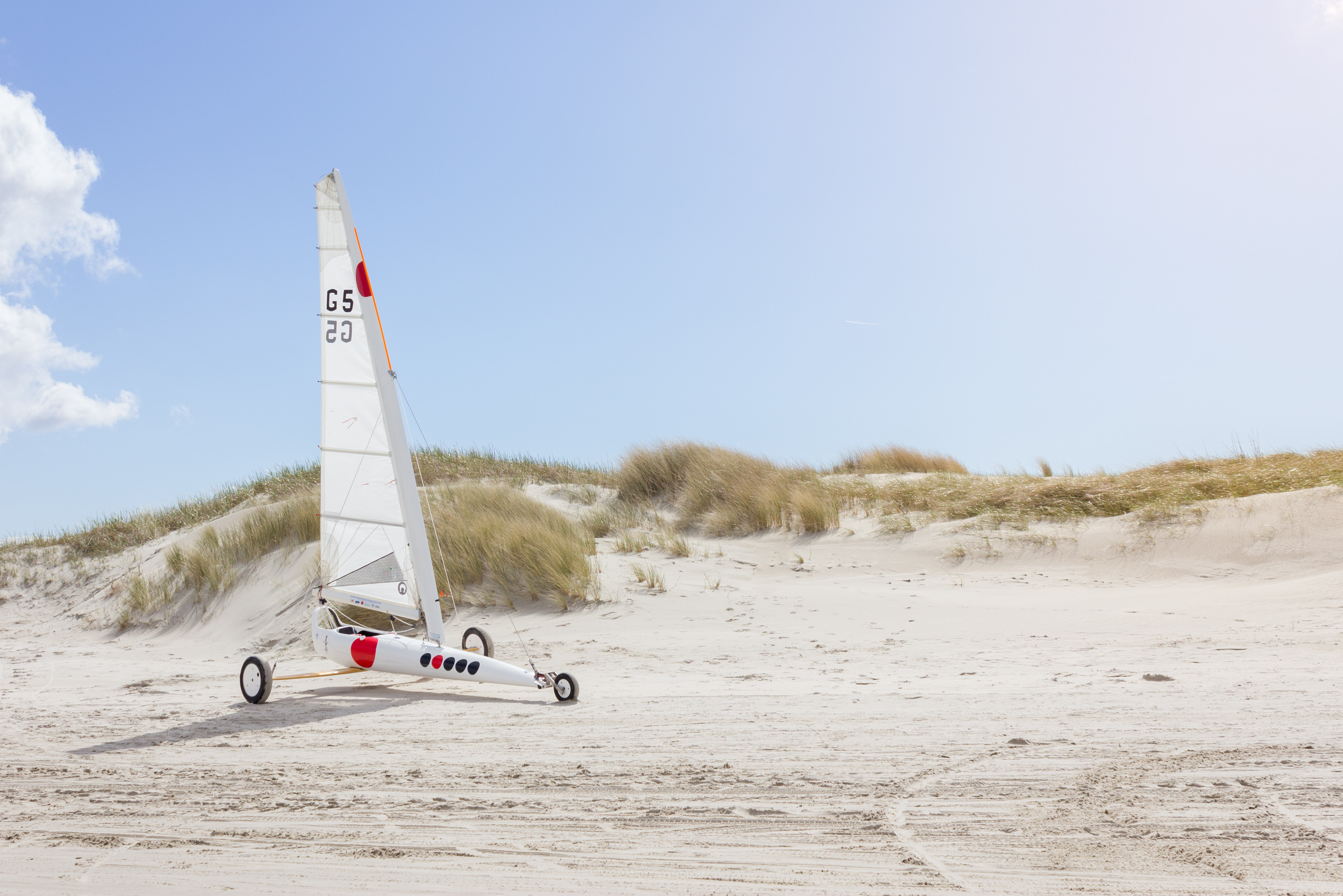 landscape photo of white sailboat with wheels on sand