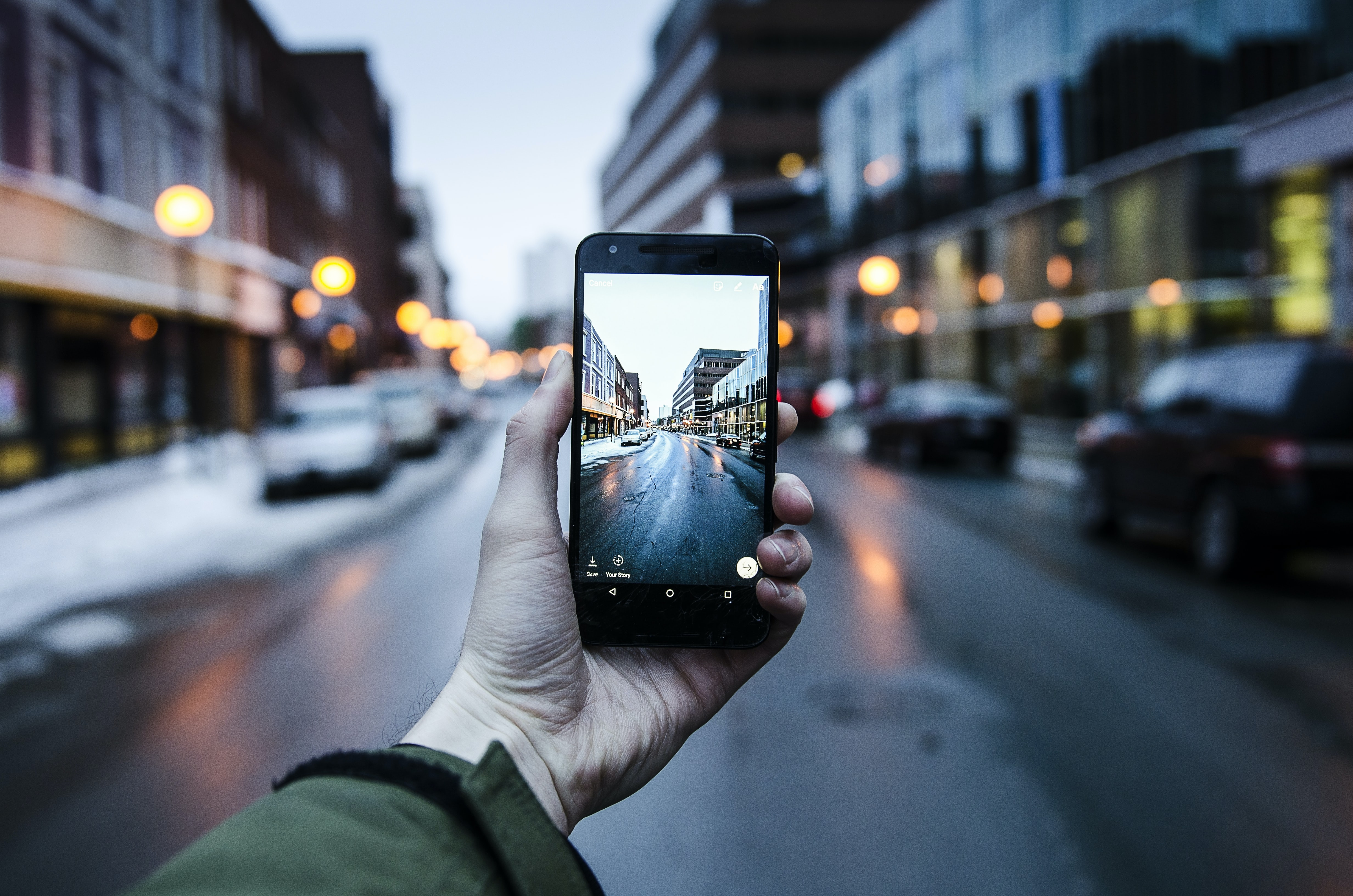 person holding iPhone while taking photo of asphalt road