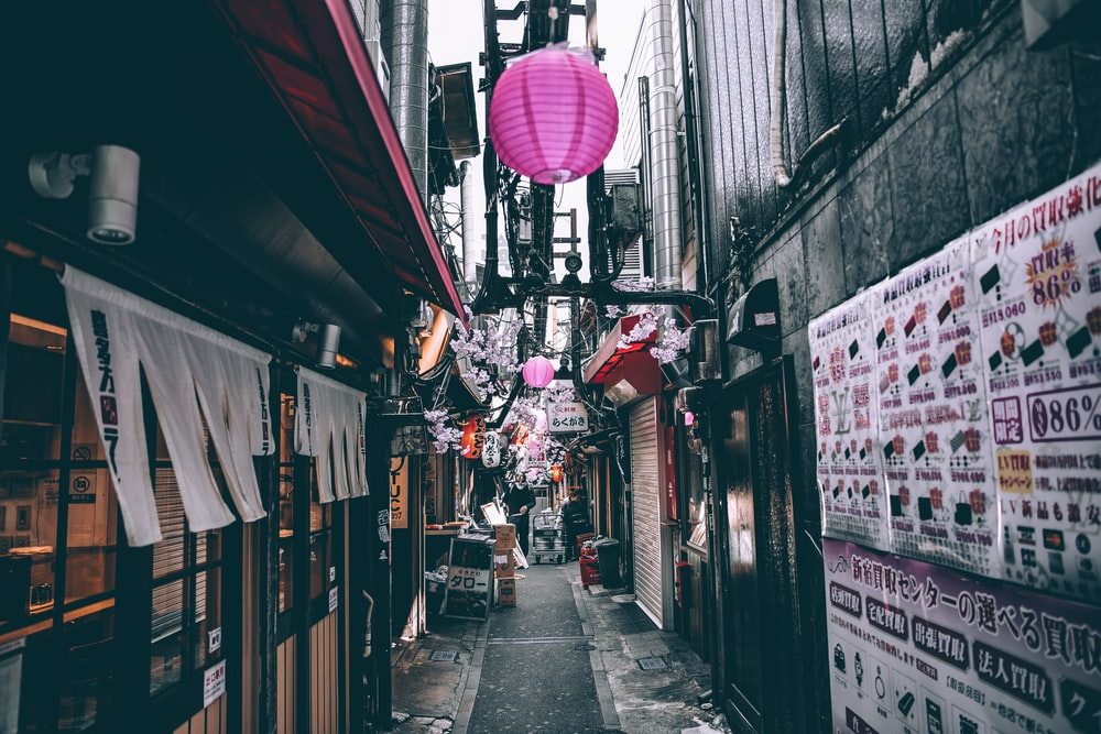 selective color photography of pathway between building with pink lanterns