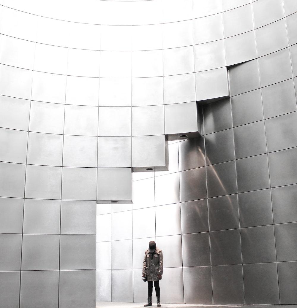 person standing under metal block building