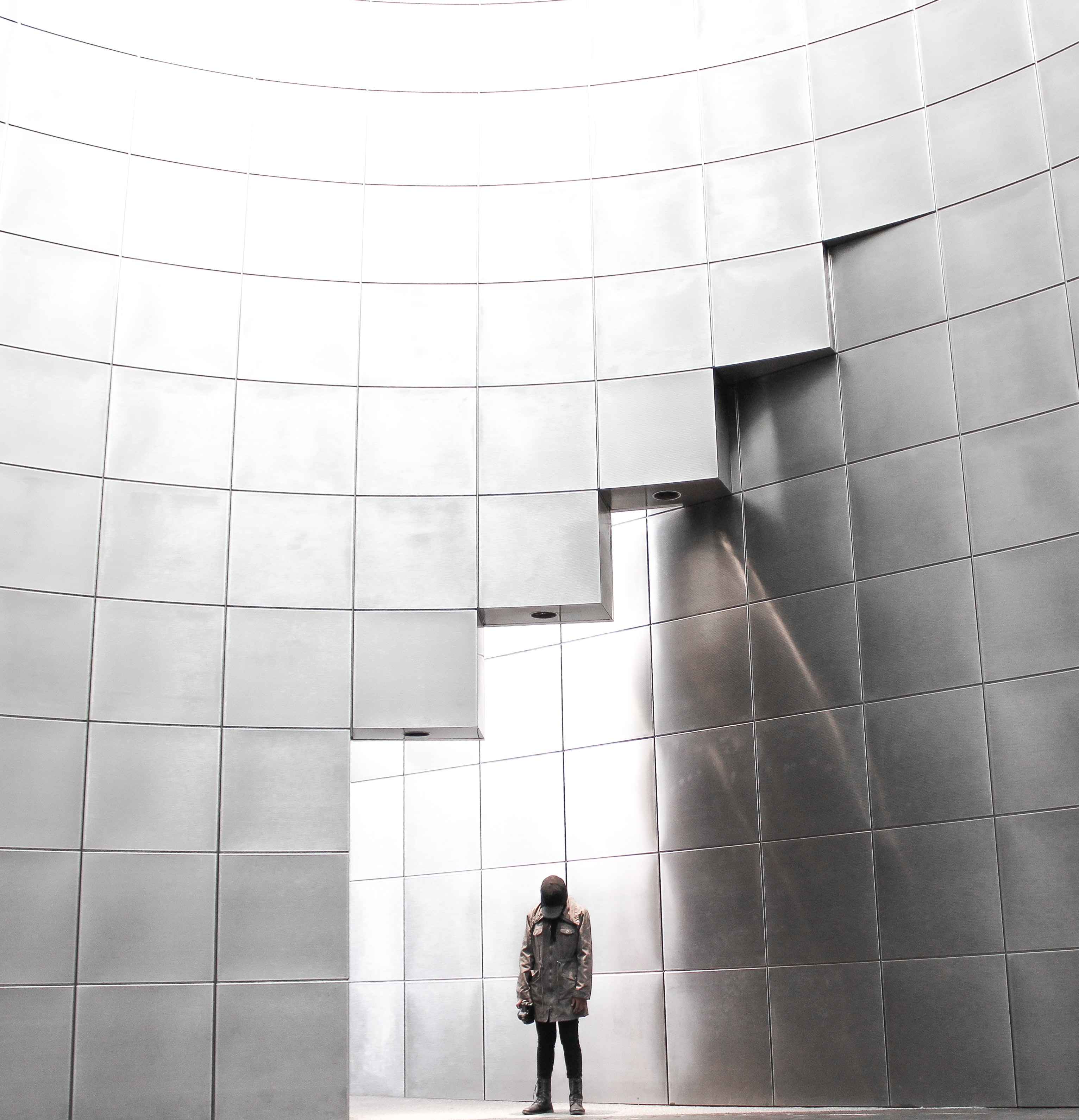 person standing under metal block building