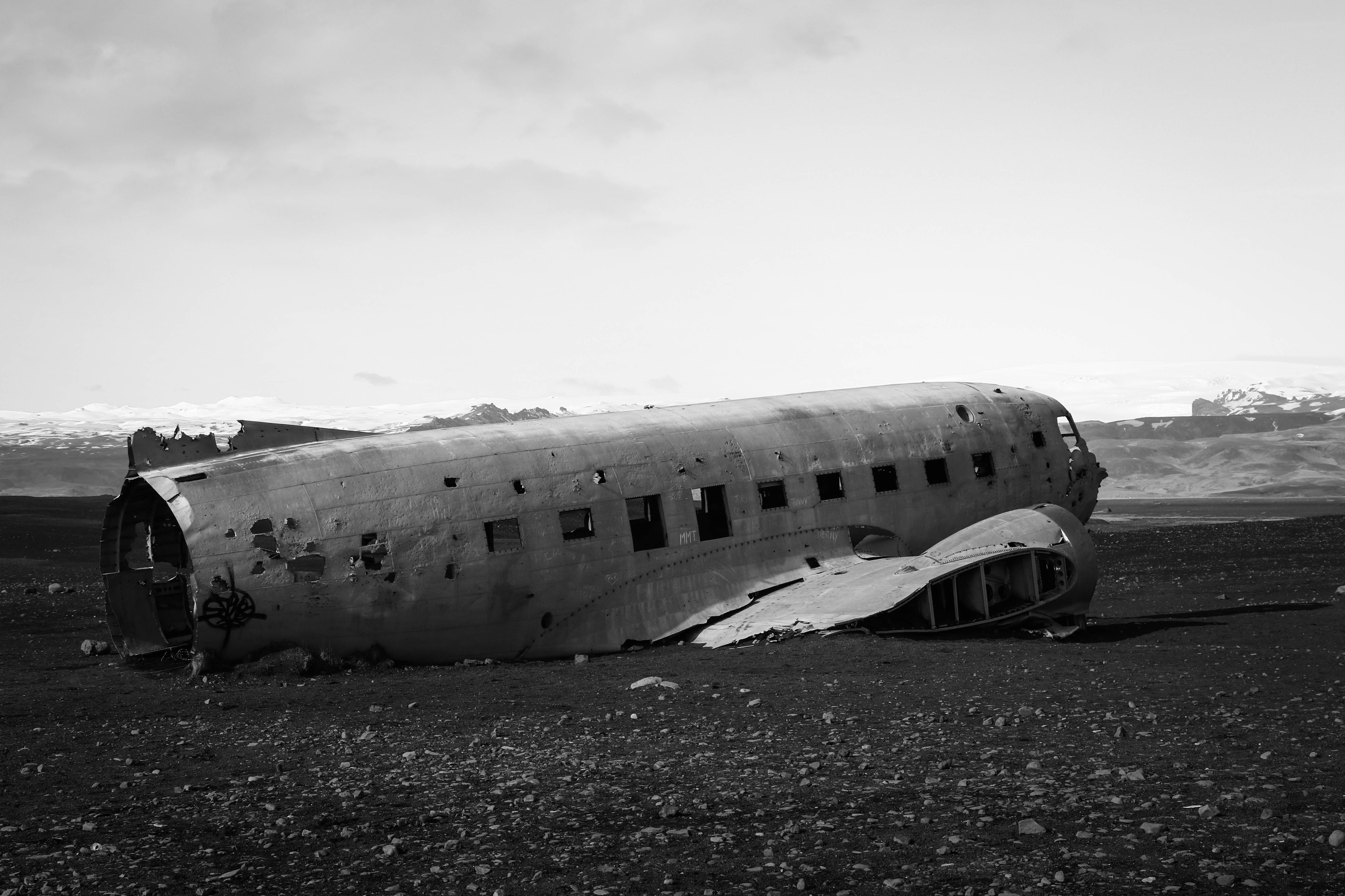 gray scale photo of airplane beside sea