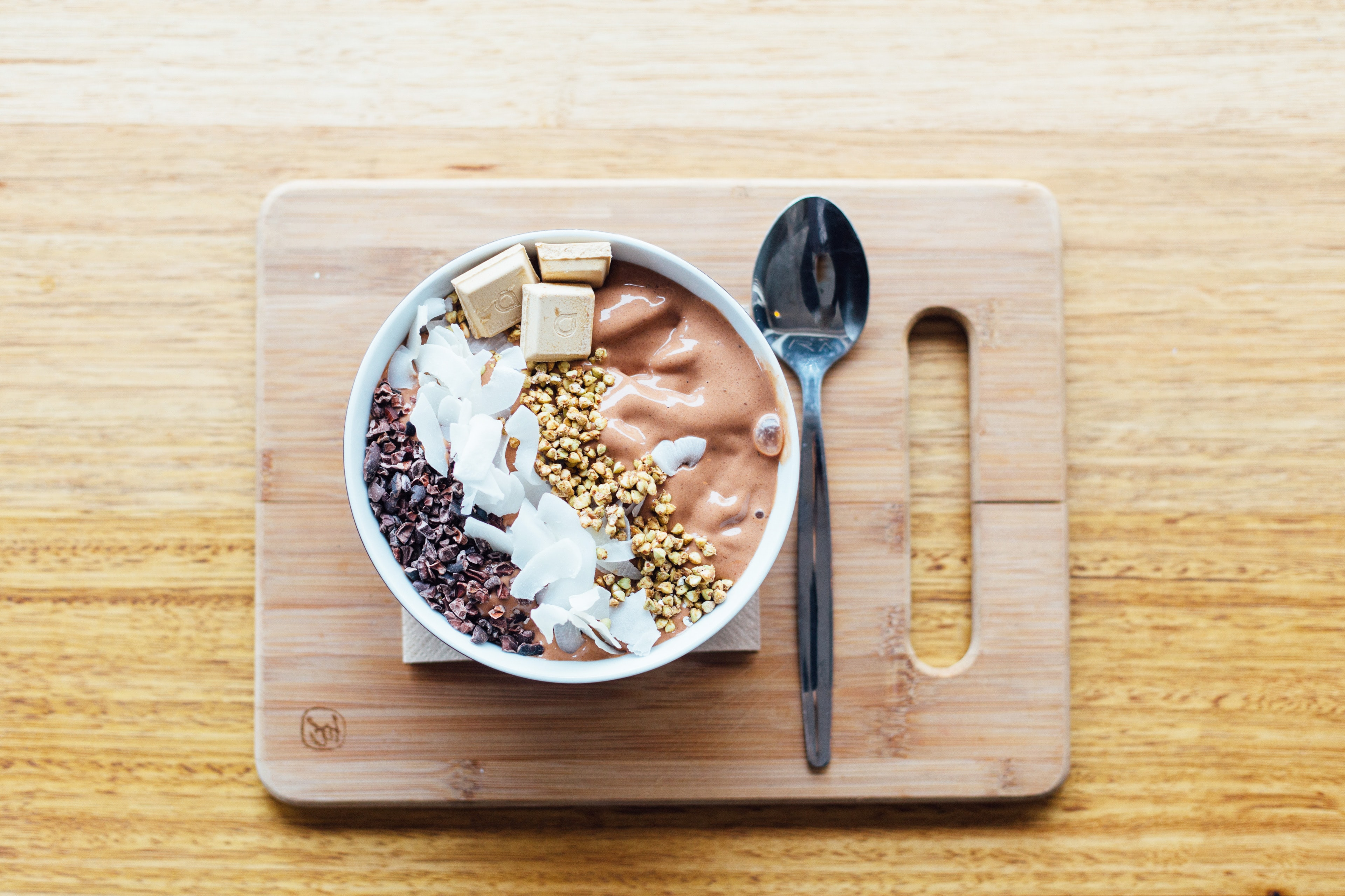 silver spoon and white bowl on brown wooden chopping board