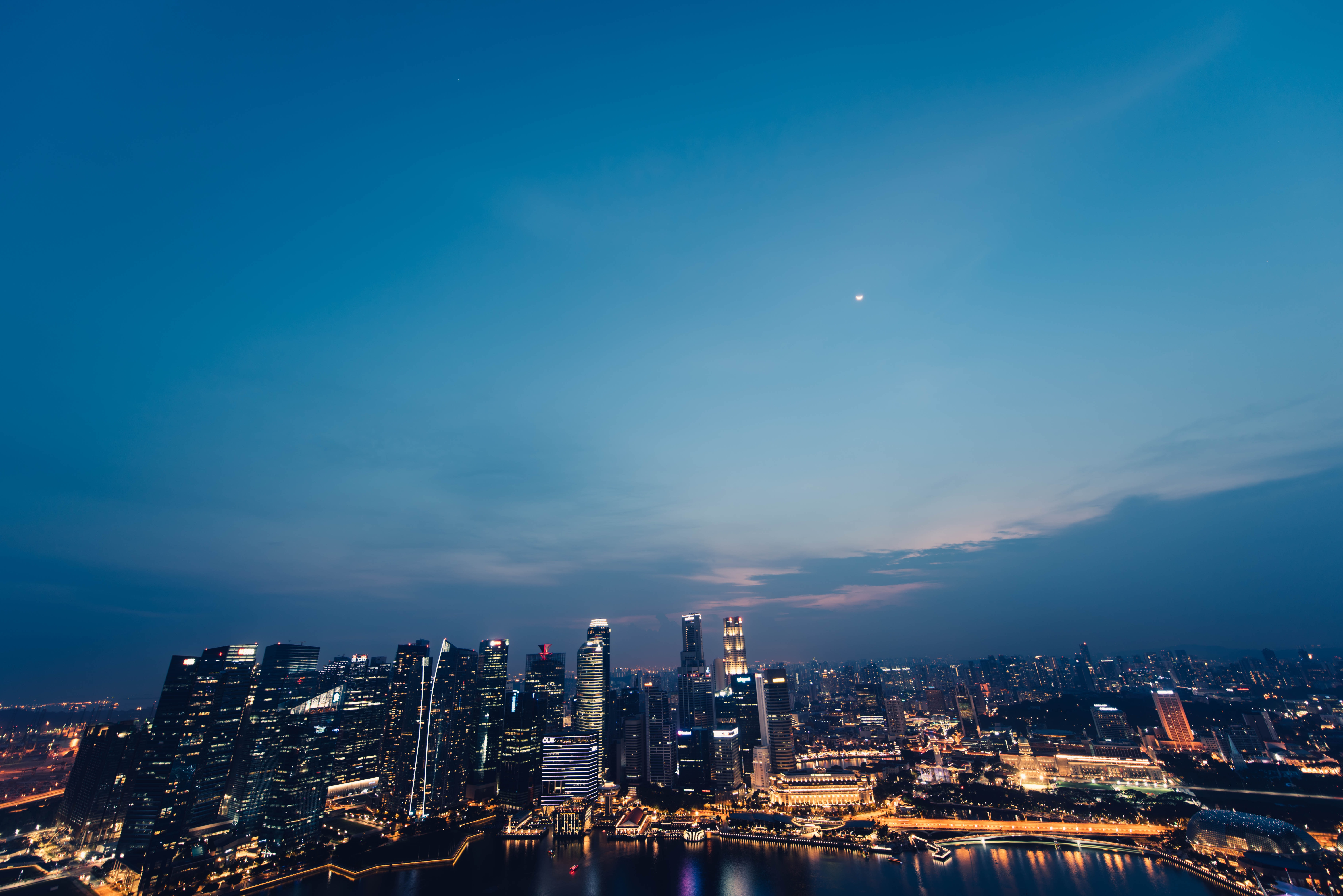 A panoramic shot of the skyscrapers and skyline of Singapore at nightfall.