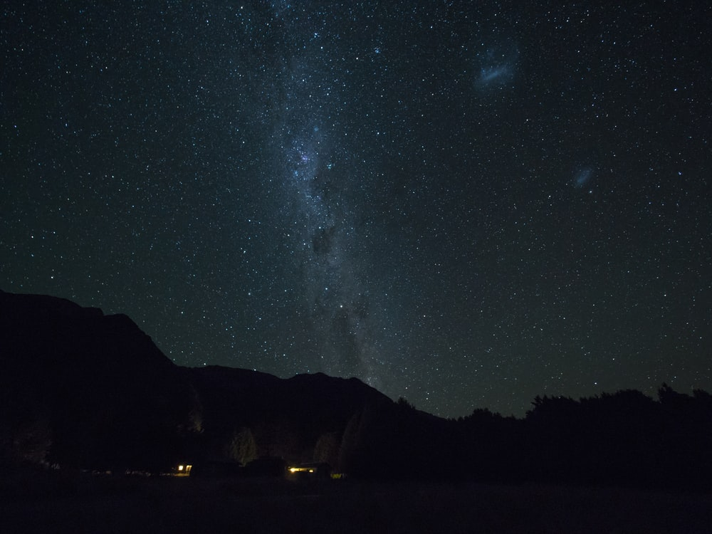 mountains and sky full of stars during night