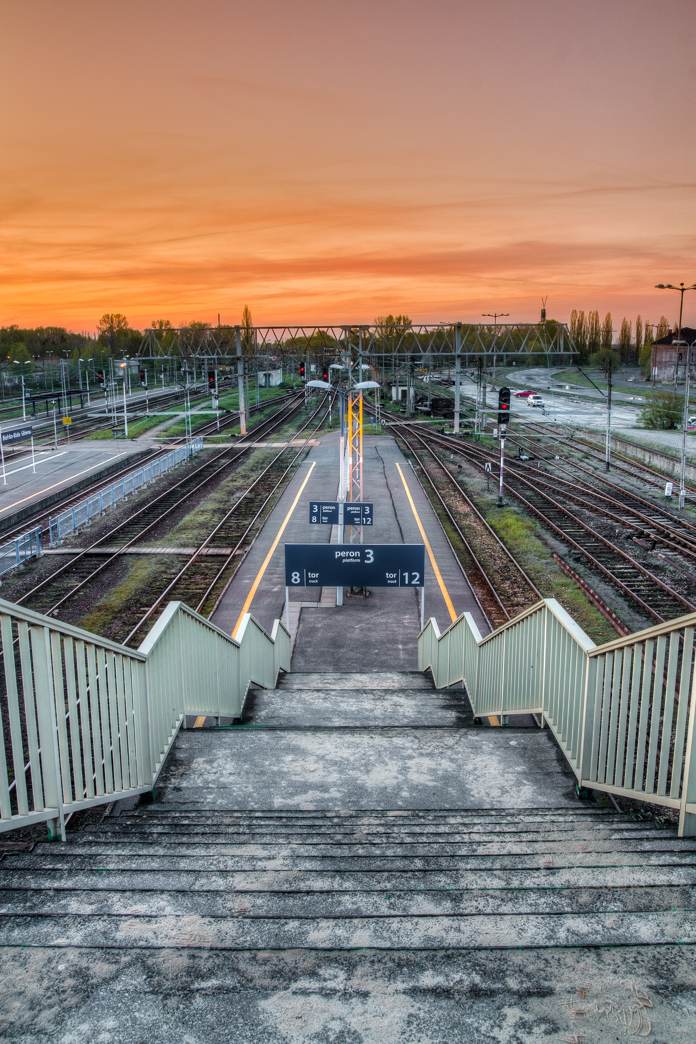 Looking down a staircase from a railway platform during the sunset