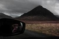 man taking photo of mountain while in car
