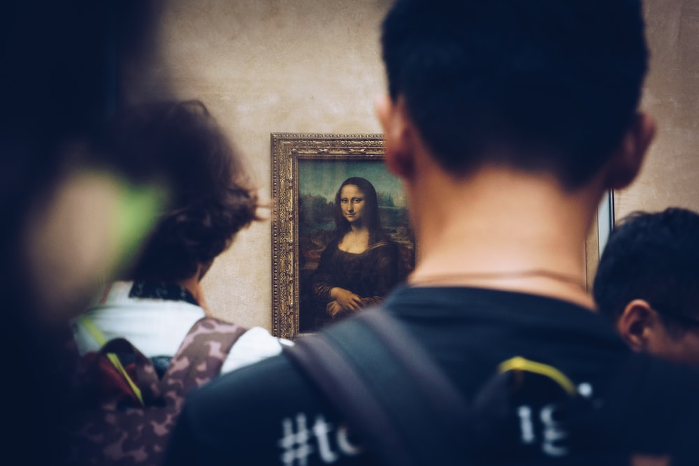 Picture from behind of people viewing the Mona Lisa in Louvre art gallery in Paris