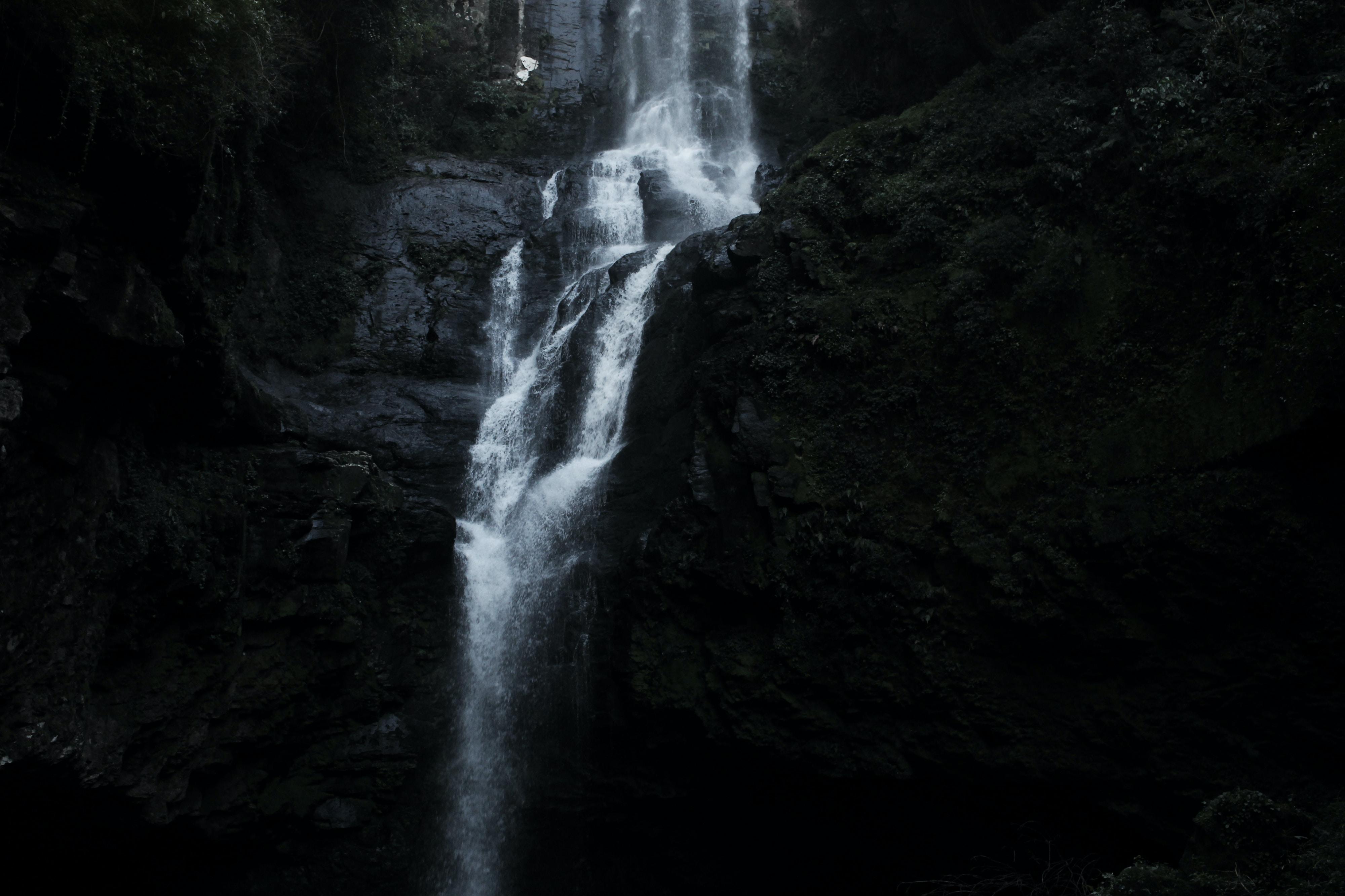 Large waterfall tumbling down a rock cliff seen through a dark filter
