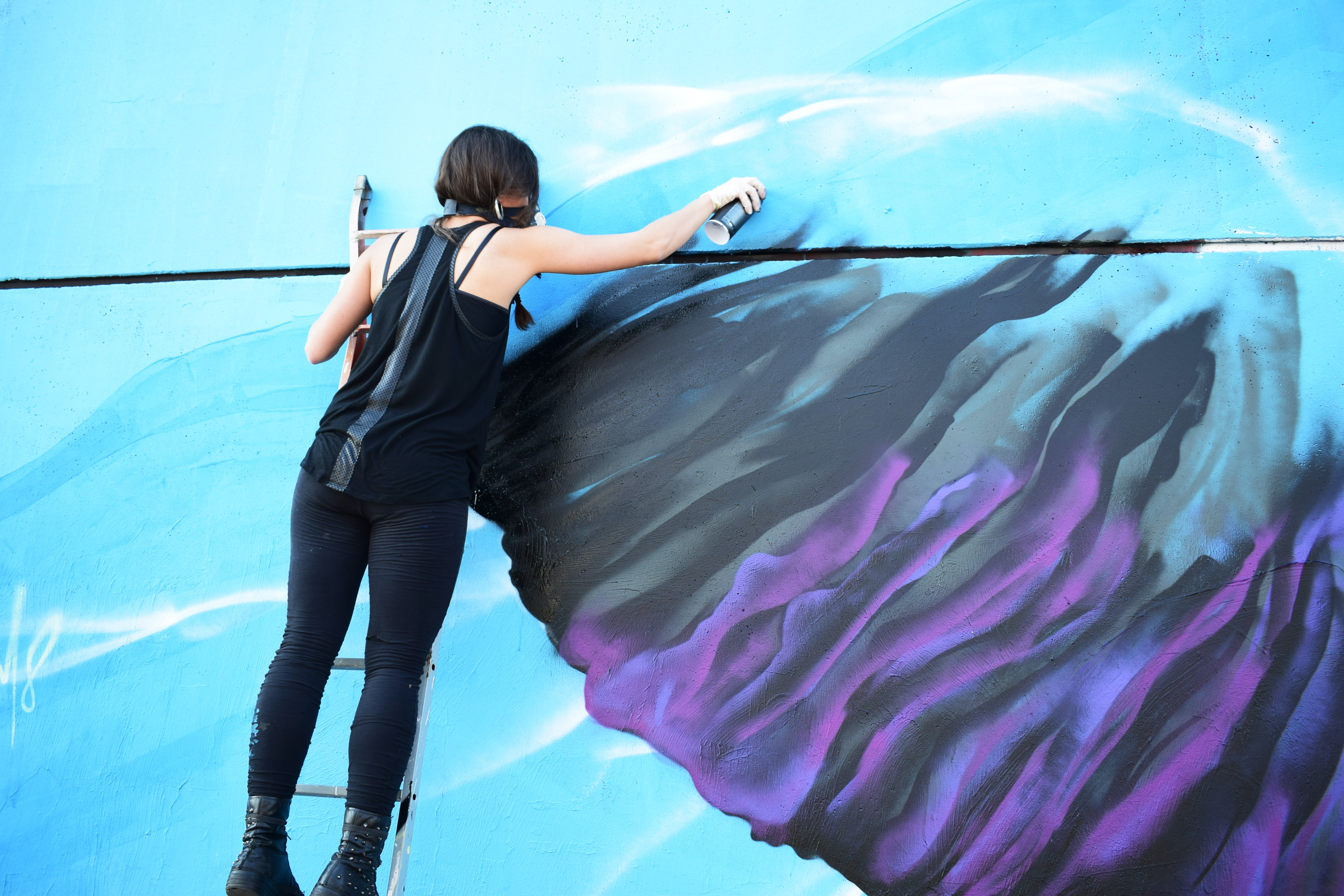 A woman making art with spray paint.