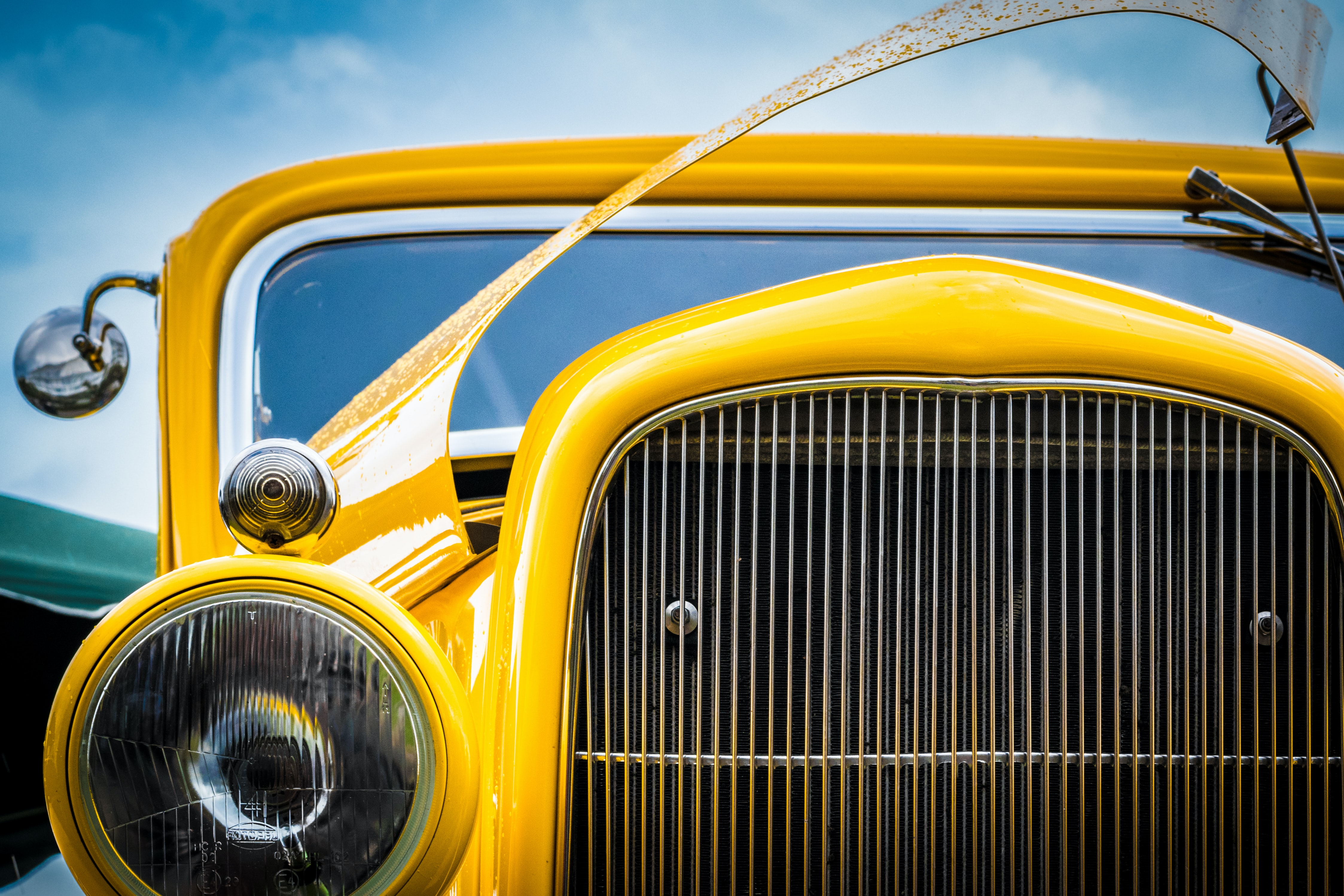 Front view of the yellow oldtimer vintage car headlight, grille, and an opened bonnet