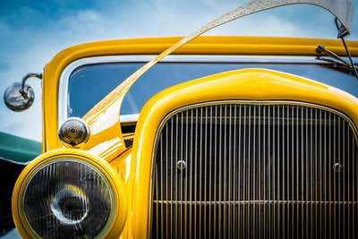 front,view,of,yellow,oldtim,vintag,car,headlight,grill,and,an,open,bonnet
