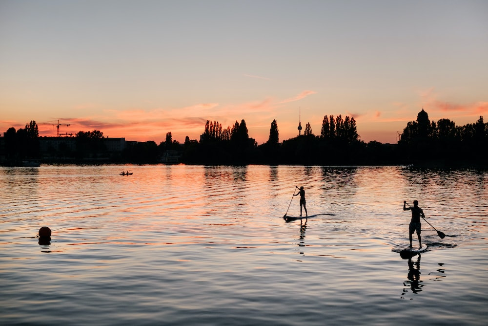 silhouette of person standing on paddle board