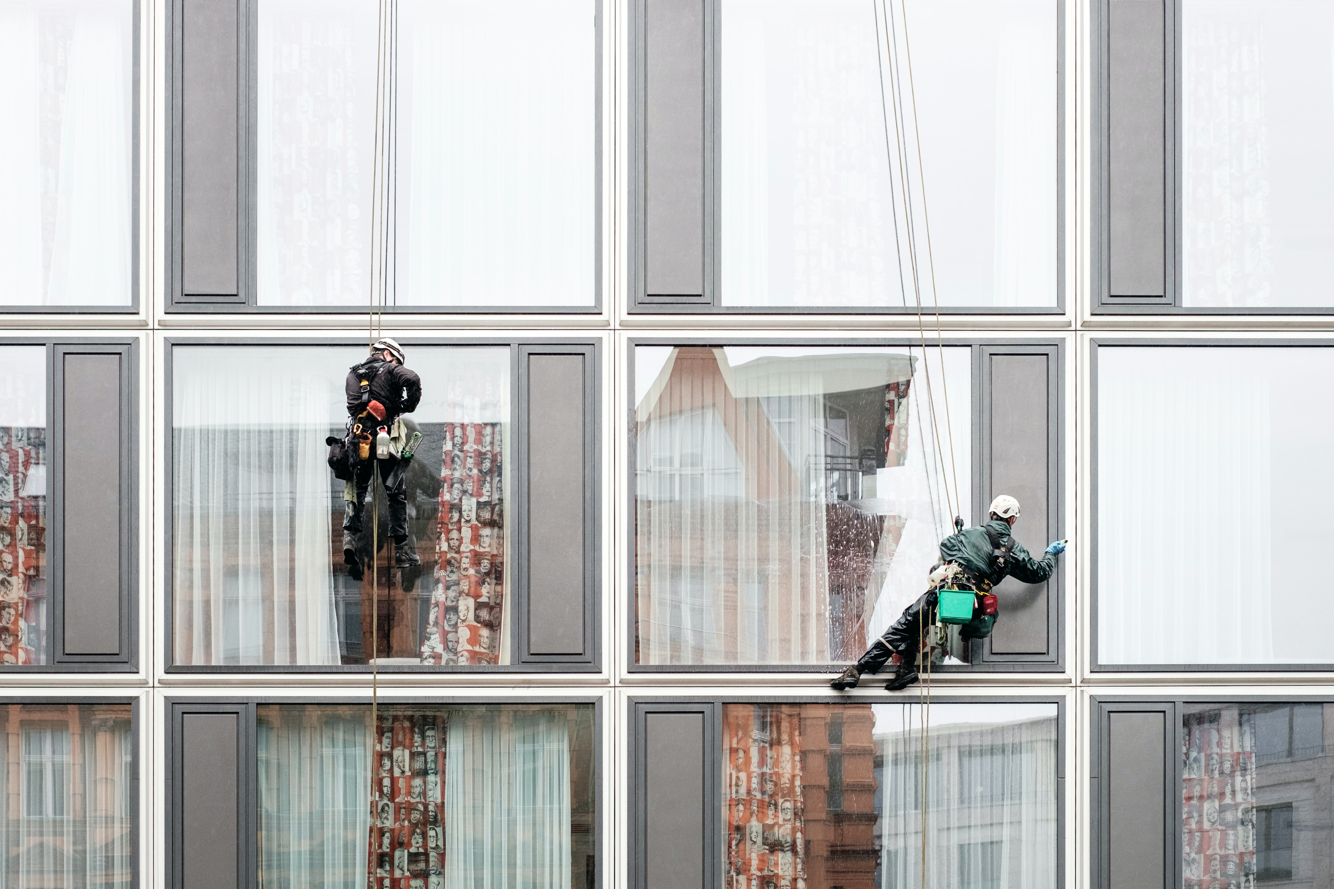 Two window cleaners cleaning the windows of a building in Berlin