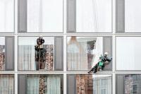 man hanging beside building window