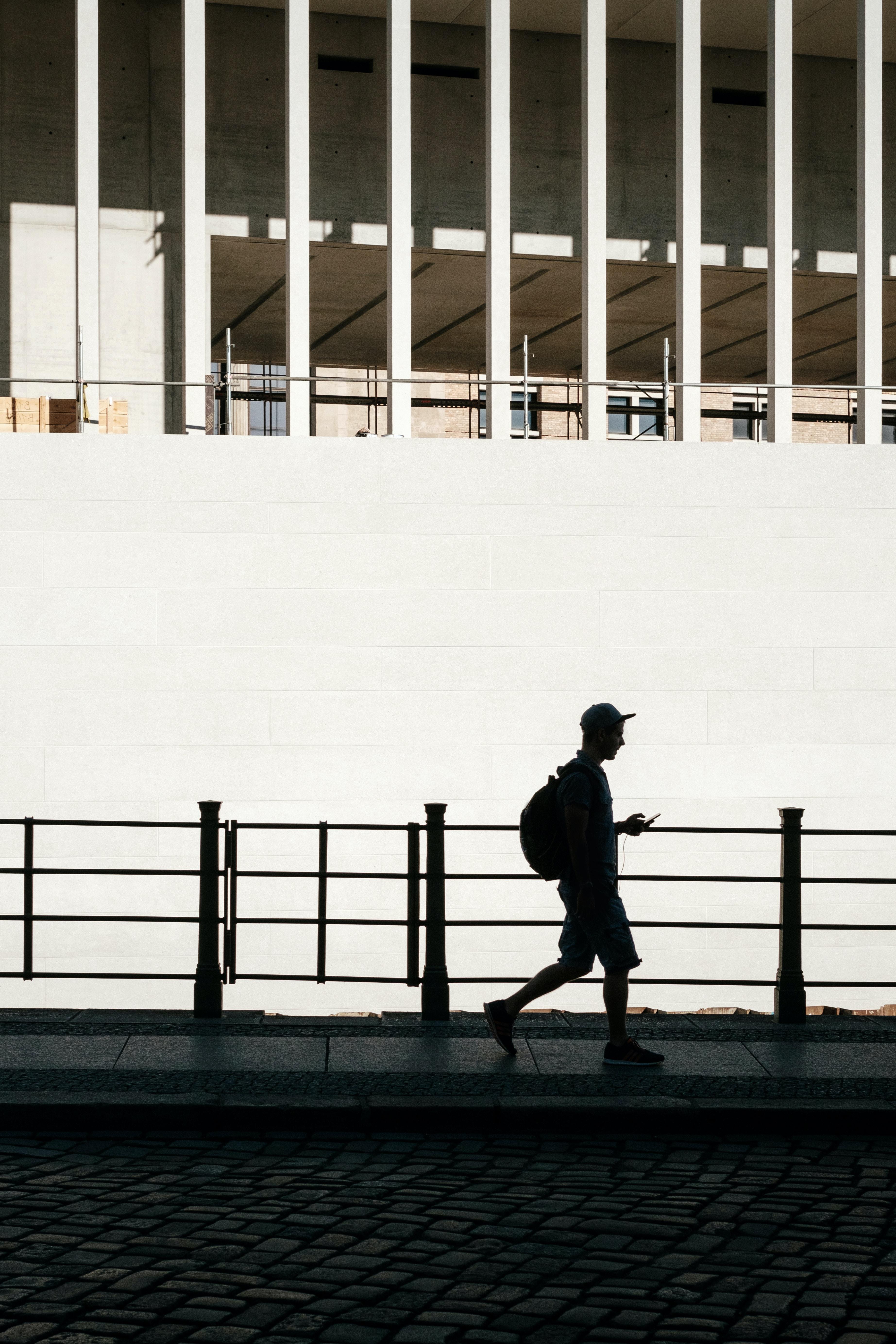 silhouette of man standing beside road rail